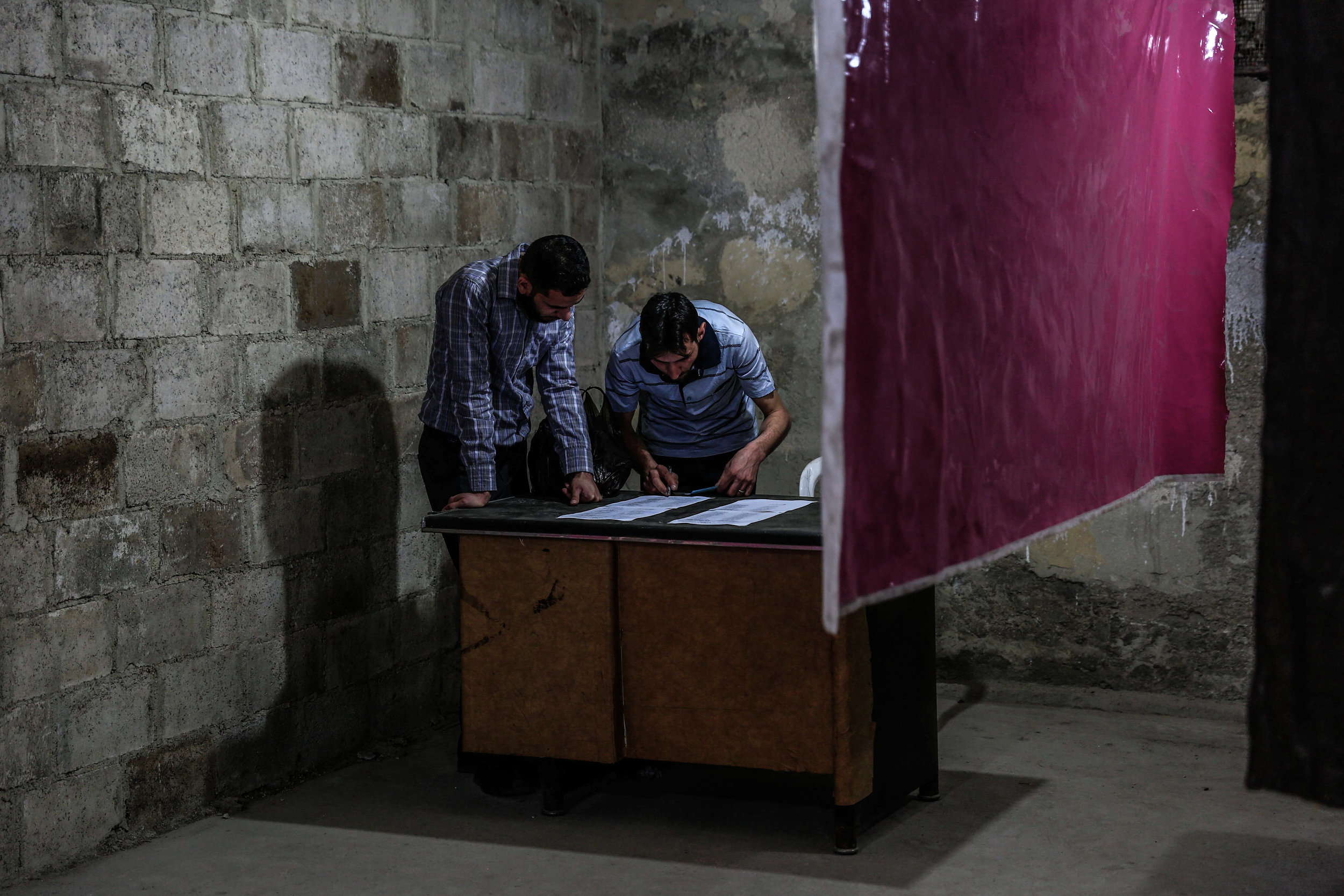 - People cast their votes in an underground basement during the election of the local council in the city of Douma in Eastern Ghouta.