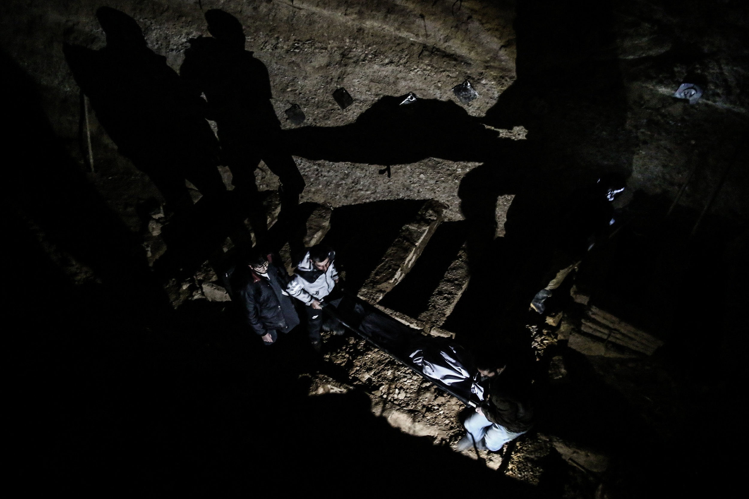Men gather to bury the bodies of a family in the city of Douma. The family, made up of two boys, their mother and their grandmother, were killed during shelling by the Syrian government forces as they were having a picnic.