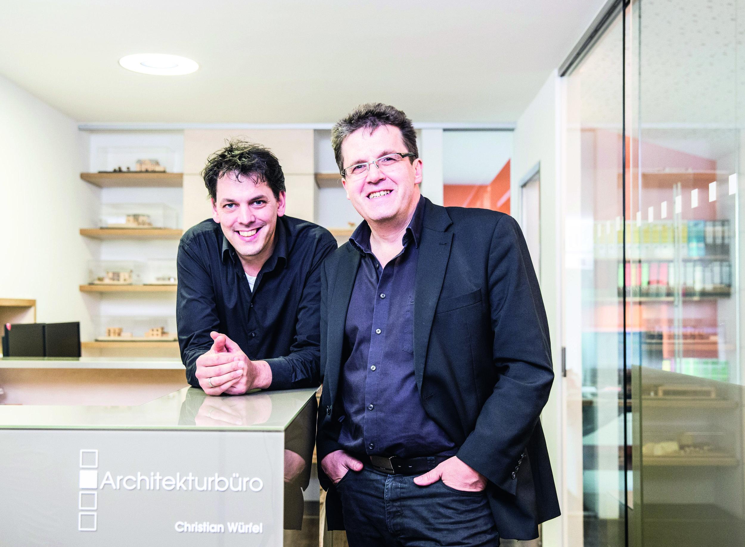 """Architekturbüro Würfel - """"Die gebaute Umwelt beeinflusst die Qualität unseres Lebens. Meine Aufgabe, schwere Konstruktionen ähnlicher Formate leichter wirken zu lassen, ist durch das Höhenspiel der Gebäude gelöst. Die moderne Interpretation des ländlichen Baustils spiegelt sich in den zahlreichen Holzelementen wider. Dadurch entsteht ein gemeinsames und harmonisches Gesamtbild."""""""