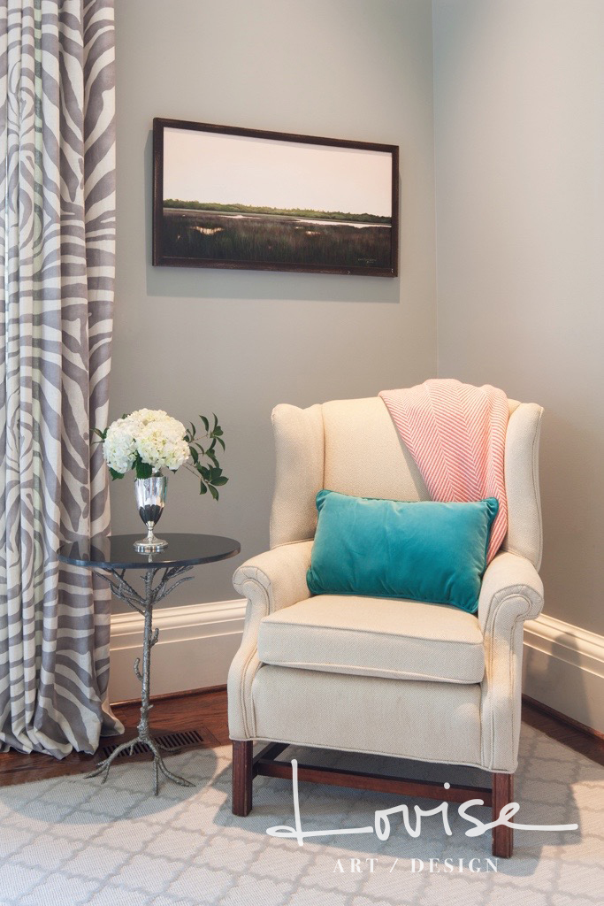White wingback chair with zebra draperies and teal and coral details