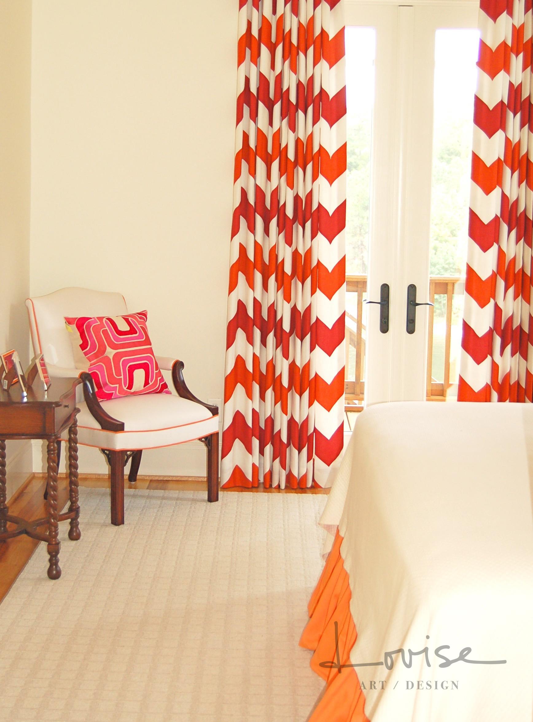 Lake bedroom with red and orange chevron draperies