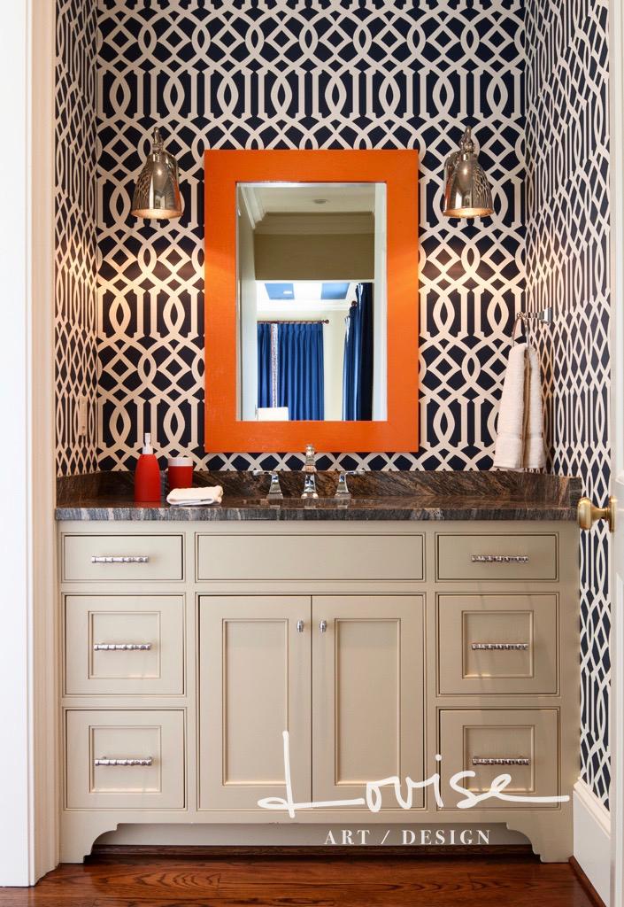 Bathroom with navy and white trellis wallpaper, orange mirror and nickel sconces