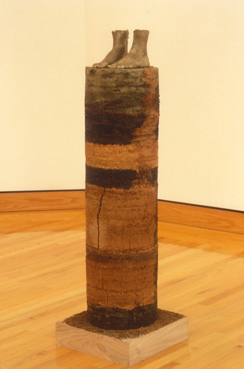 "CORE SAMPLE: SELF PORTRAIT  1994 earth from every place I've lived, 1"" equals 1 year, earth from Missouri, Louisiana, Illinois, Alabama, Minnesota, Maine, Missouri,   Glue, life cast bronze of my feet , cylinder, 43"" x 12""."