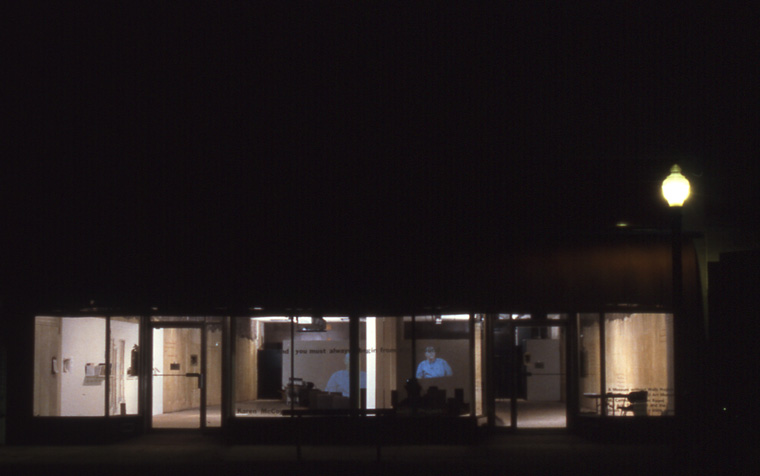 Night view of outside of downtown storefront location of installation in old Woolworth's building, installation and video projection  ( CONVERSATIONS ABOUT DEKALB).   walls stained with local pigments and lettered with text, earth furrows and rammed earth solids, 2,000 square feet.