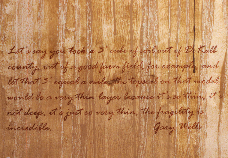 View of walls stained with local pigments and lettered with text from Gary Wells interview.