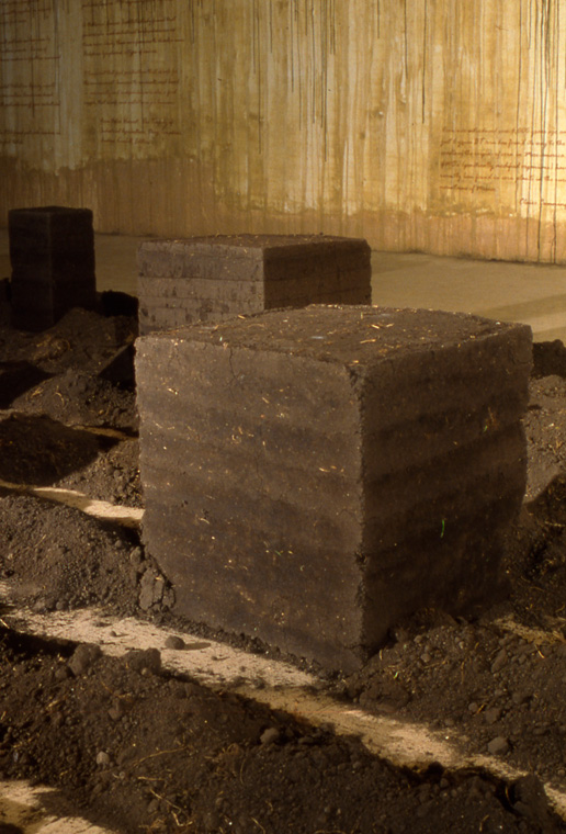 """Detail of rammed earth cube and furrows of local topsoil. cube 18 x 22 x 18""""."""