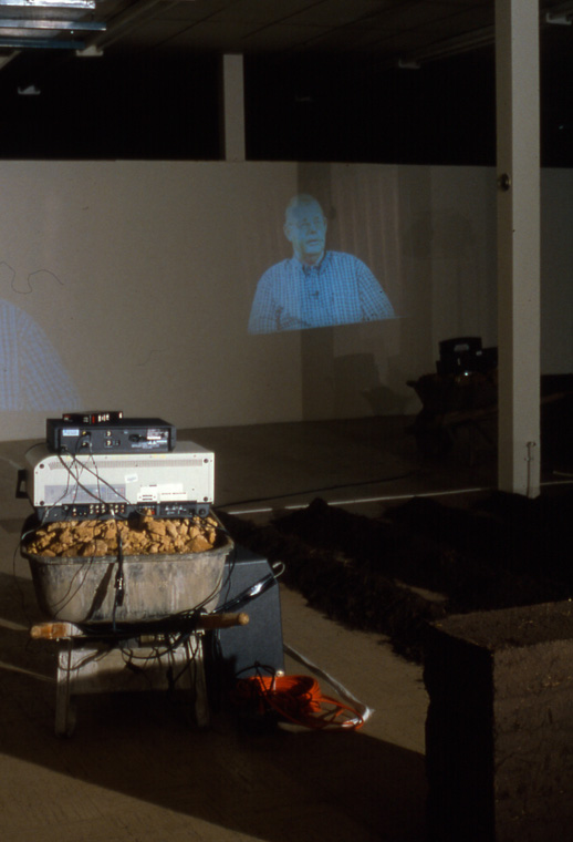 Detail of video projector resting on wheelbarrow of earth clods.