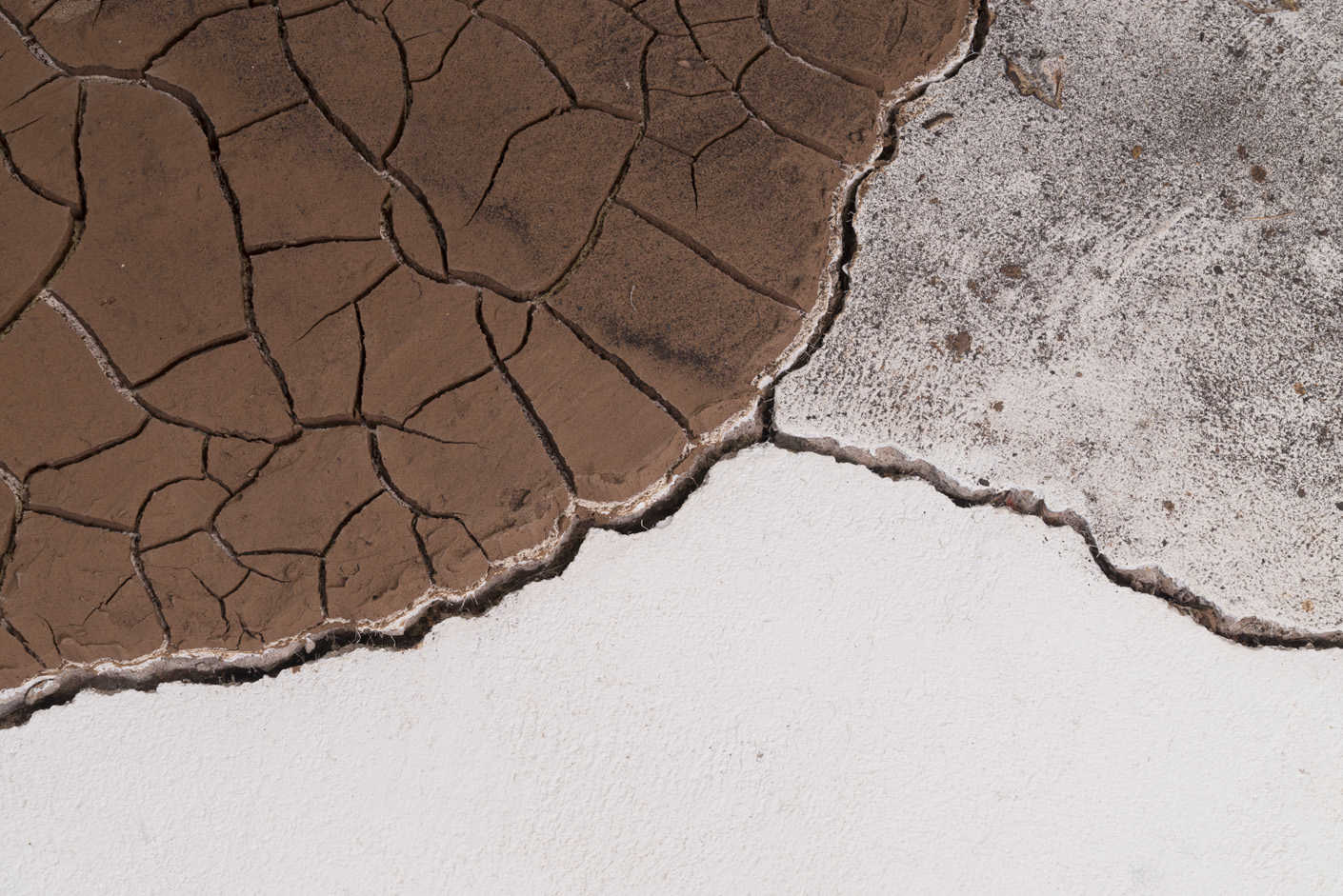 Installation detail of cracked earth and ash bounded by cracks in gallery floor.