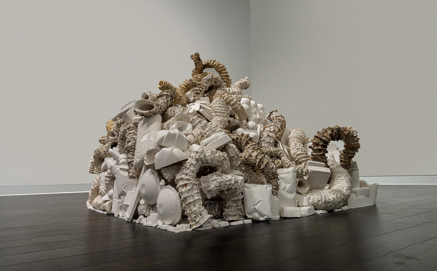 """Seemingly Unconnected Events Cubed (V5)  2007- 2014 (ongoing)  Hundreds of plaster casts of organic forms interwoven and interconnected with consumer goods casts, 4 x 4 x 40"""" highest point  Installation at Epsten Gallery, Village Shalom, metropolitan Kansas City, MO, 2014   Photo: E.G. Schempf"""