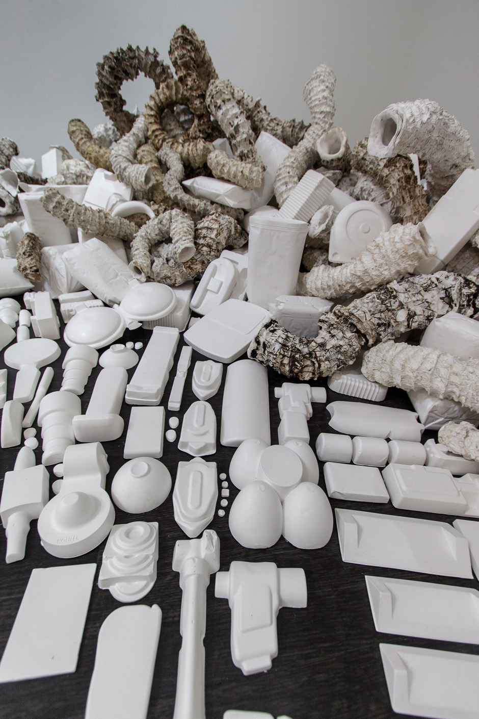Seemingly Unconnected Events V4  2007- 2014 (ongoing)  DETAIL.Hundreds of plaster casts of organic forms stacked and interlaced with consumer goods casts, 15 x 7 x 2.5'  Installation for Re Imagine, Three Person Exhibition, Epsten Gallery, Village Shalom, metropolitan Kansas City, 2014   Photo: E.G. Schempf