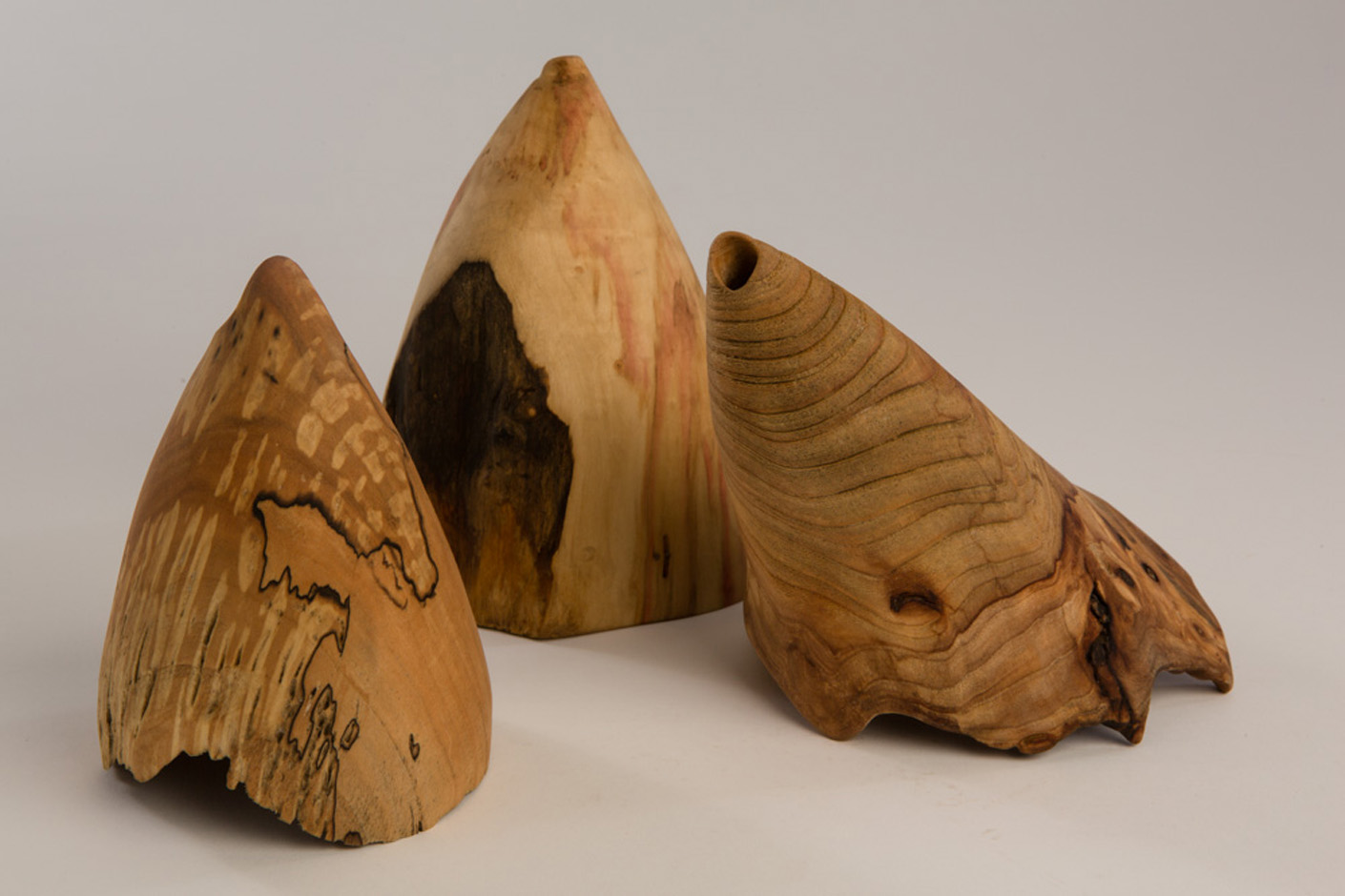 "L-R, The Beak, Maple, beeswax. linseed oil, 4.25"" diameter x 6.75"" high, Dark Front, Box Elder, beeswax. linseed oil, 4"" diameter x 7"" high, and Elmo. Elm, beeswax. linseed oil, 5.5"" diameter x 8.75"" high Photography: Stacey Evans"