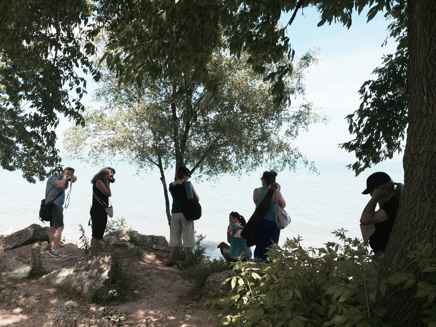 Listening to waves striking the rocks at Hartigan Beach, ten hand carved wooden burl trumpets used by participants, walk planned and led by Karen McCoy, sponsored by Alternative Spacetime 1300 (artist residency), Chicago, IL. (photo: Caro d'Offay)