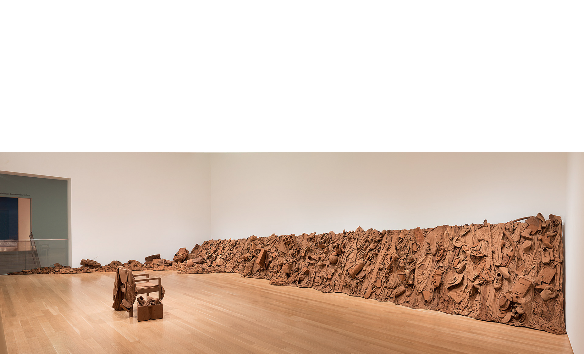 Overview,  Consuming Questions , 2017-18, an avalanche of consumer goods encased in Missouri red subsoil (clay) stabilized with PVA, wooden armature in 6 sections + floor sections.