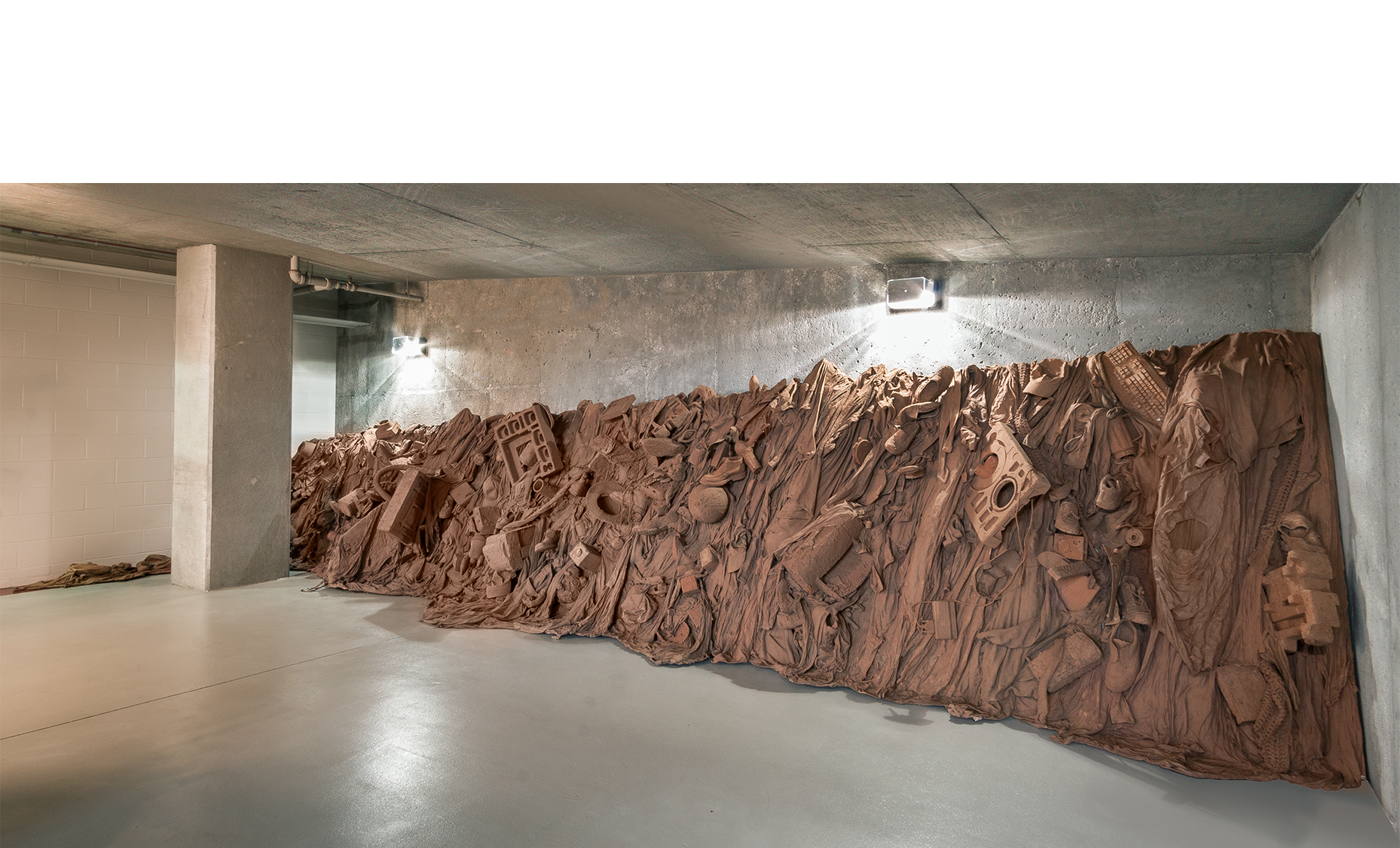 """Consuming Questions  2016  contemporary consumer goods encased in red Missouri mud stabilized by PVA  26'l x 5' average height x 40"""" d.  Photos: E.G. Schempf"""
