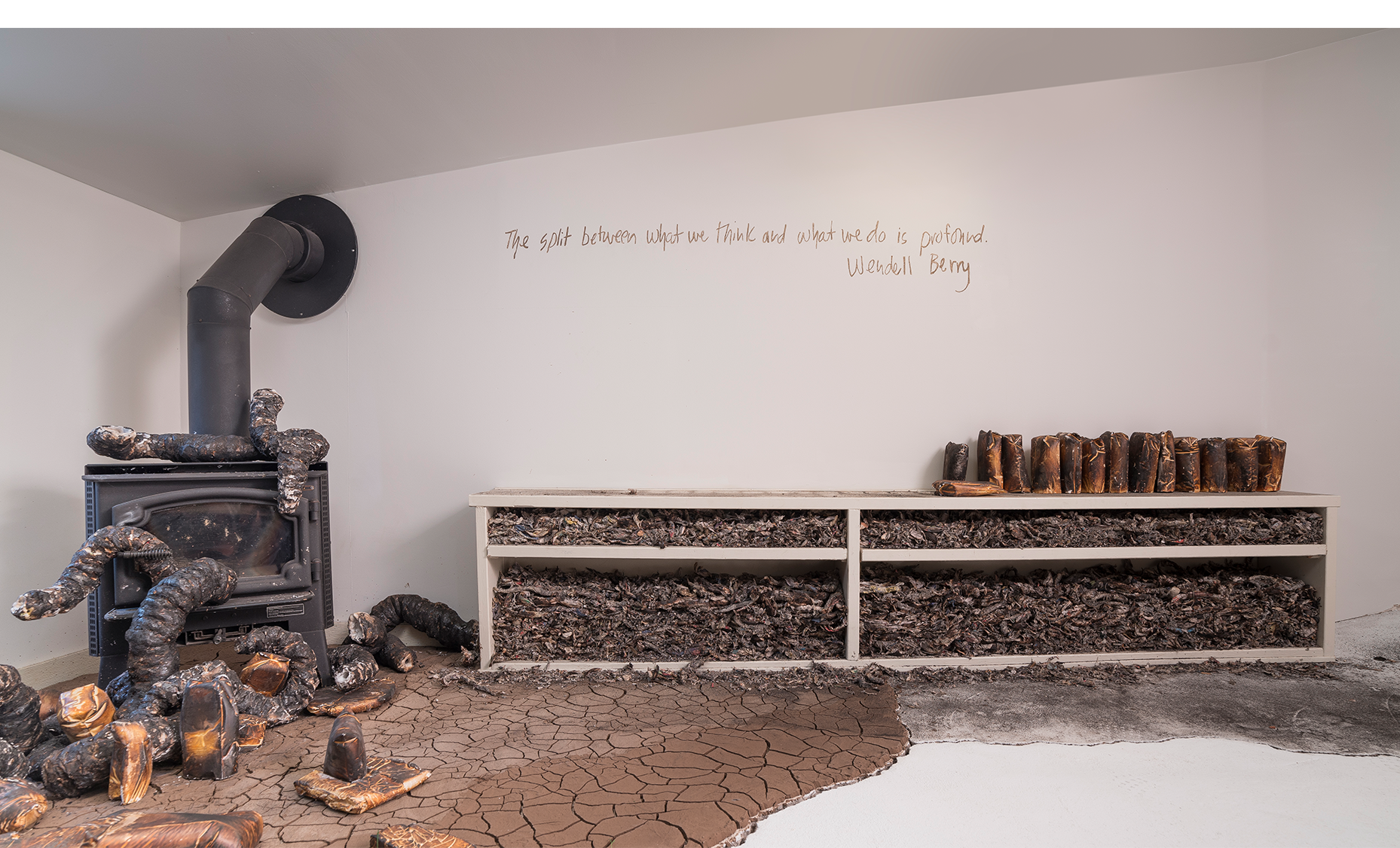 Installation detail with wood burning stove, charred newspaper fragments rammed into bookshelf, and cast plaster organic forms with charred consumer goods casts, cracked earth and ash. Wall texts drawn in Kansas mud, Wendell Berry.