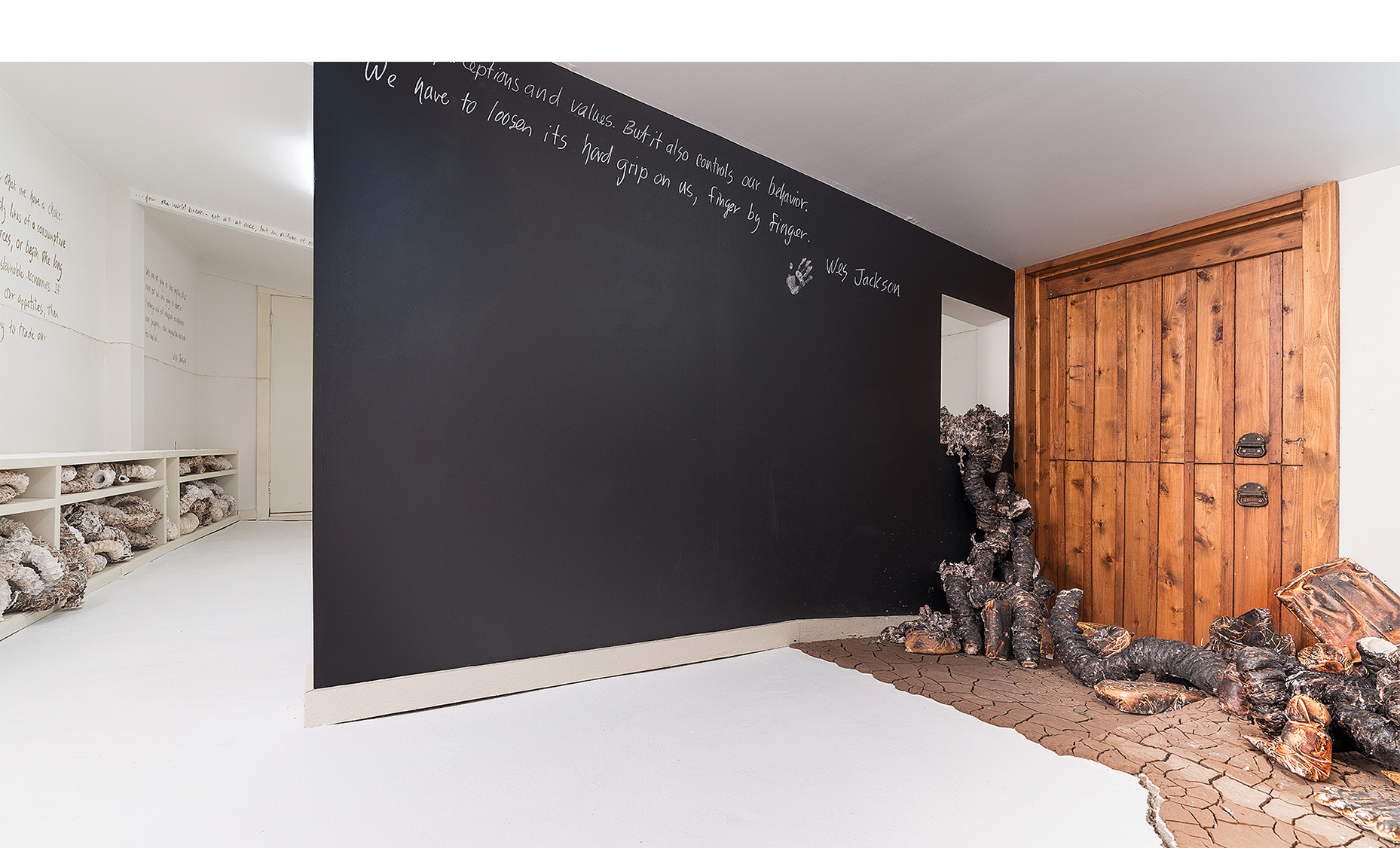 """Installation detail of charred organic forms """"climbing"""" through window, cracked earth and participatory blackboard wall with text by Wes Jackson."""