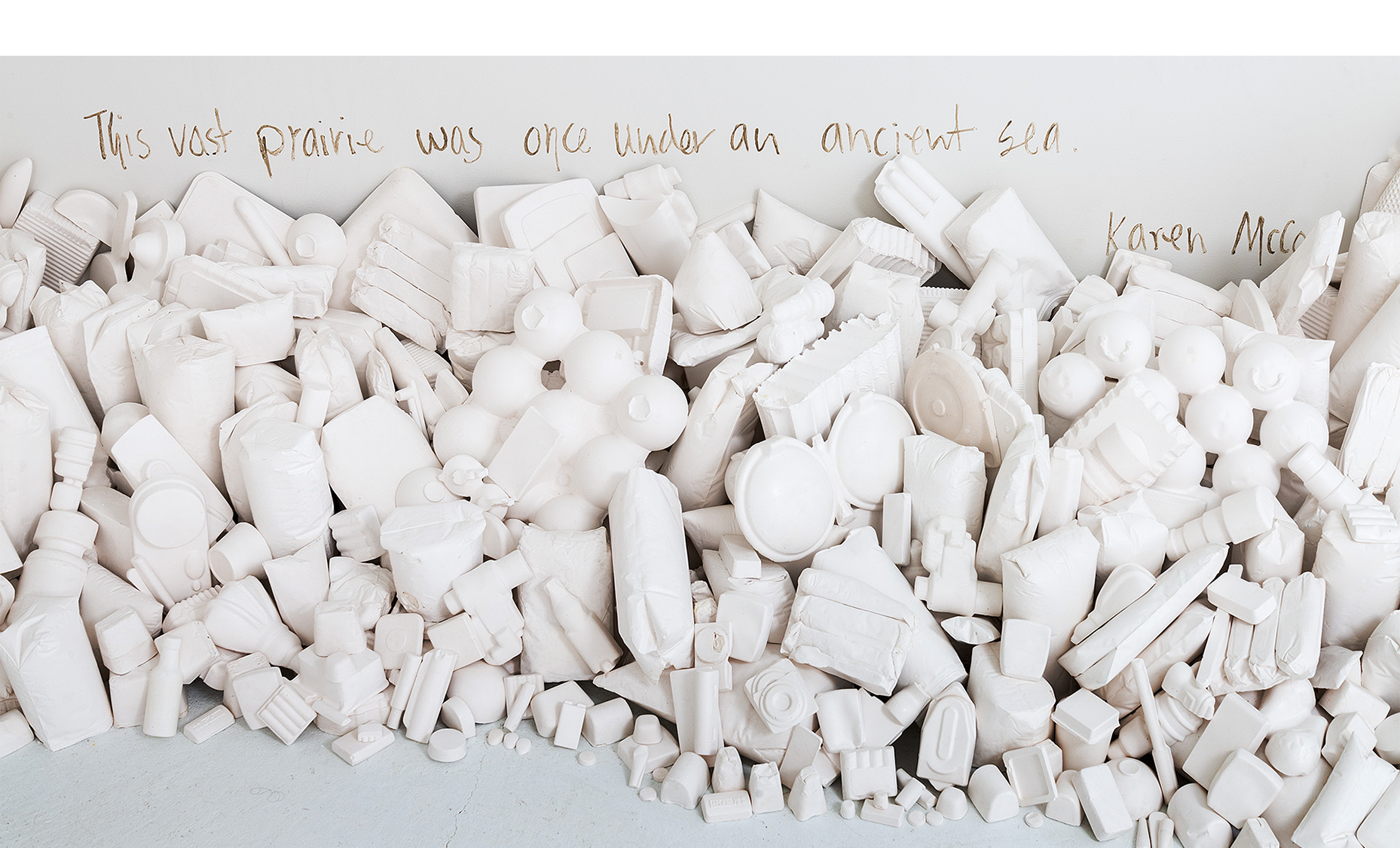 """Installation detail of consumer goods casts """"washed up"""" against the walls with text."""