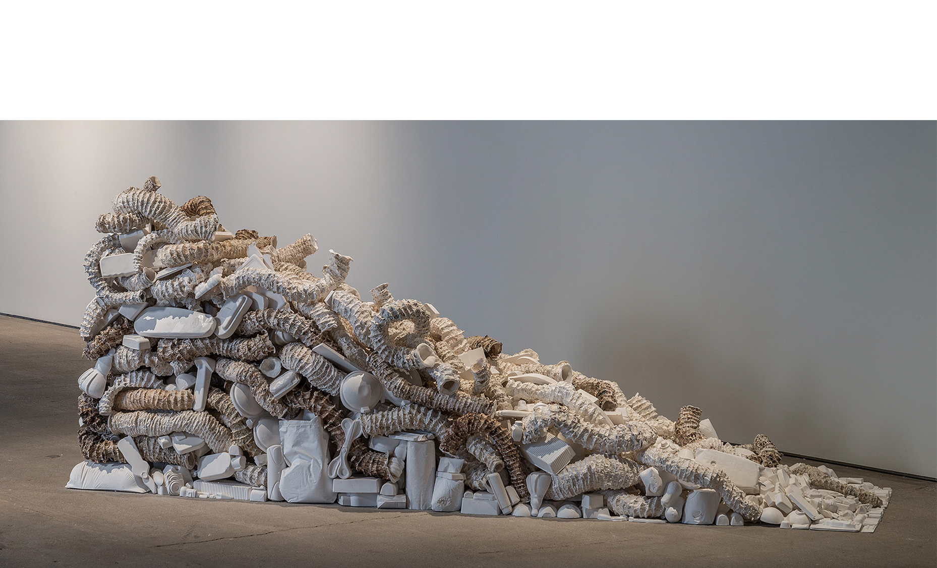 """Seemingly Unconnected Events: The Wedge  2007- 2015  Hundreds of plaster casts of organic forms interwoven and interconnected with consumer goods casts*, 90 x 30 x 45"""".  Installation at H&R Block Artspace, Kansas City, MO, Fall 2015.   Photo: E.G. Schempf"""