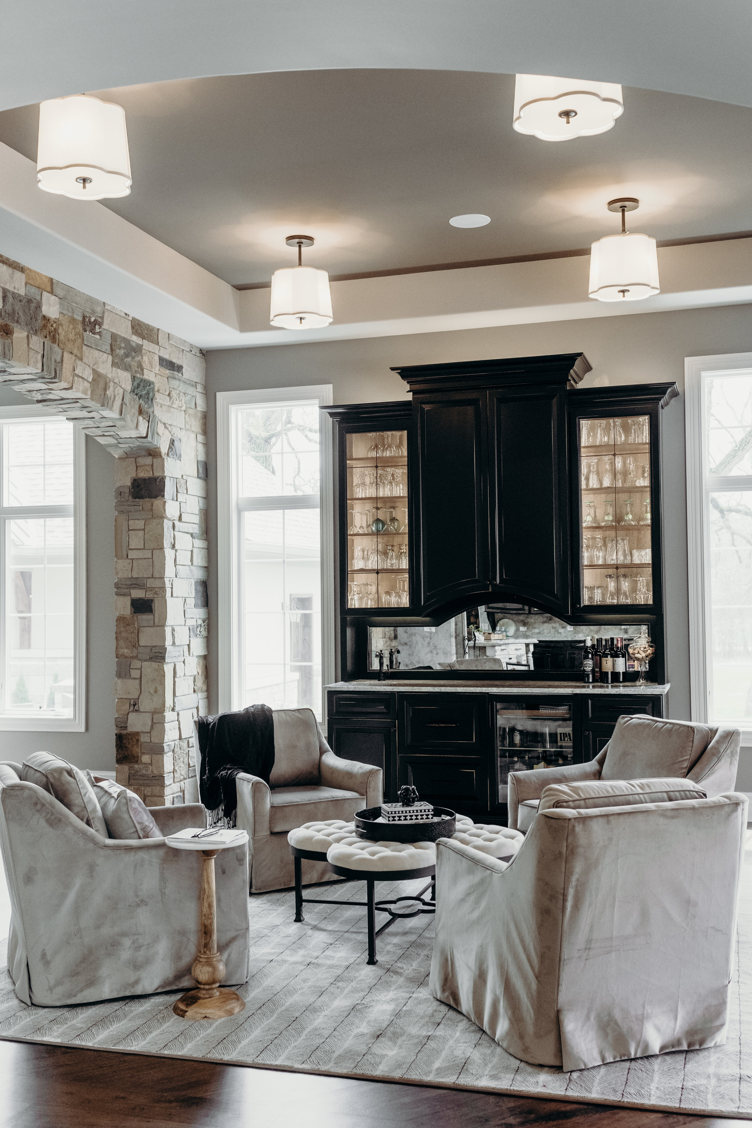 Lounge room with velvet swivel chairs, dark cabinets, and semi-flush mount lighting.