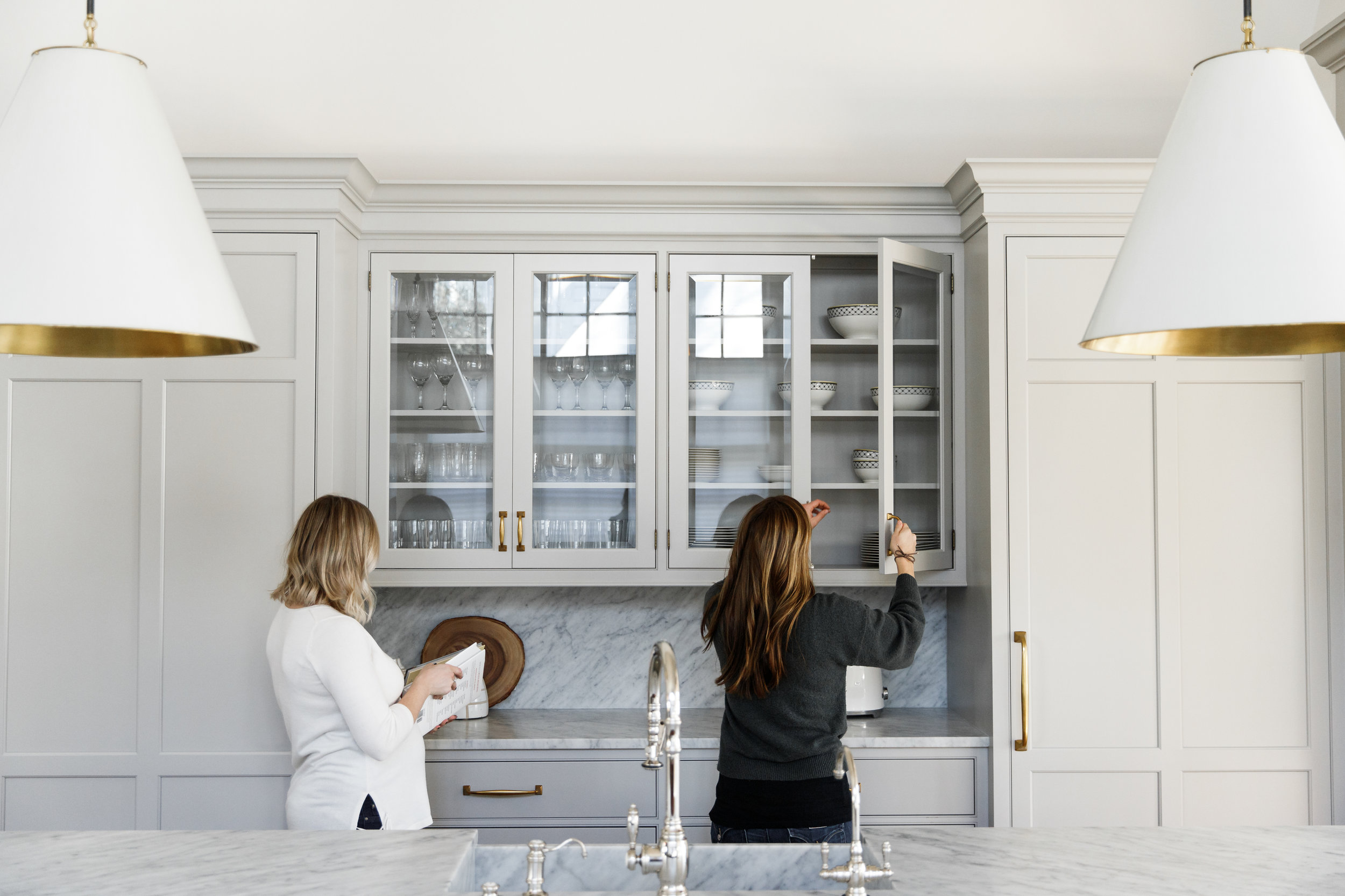Light gray cabinets with gold hardware, Circa pendants and full height honed Carrara Marble countertops with backsplash.