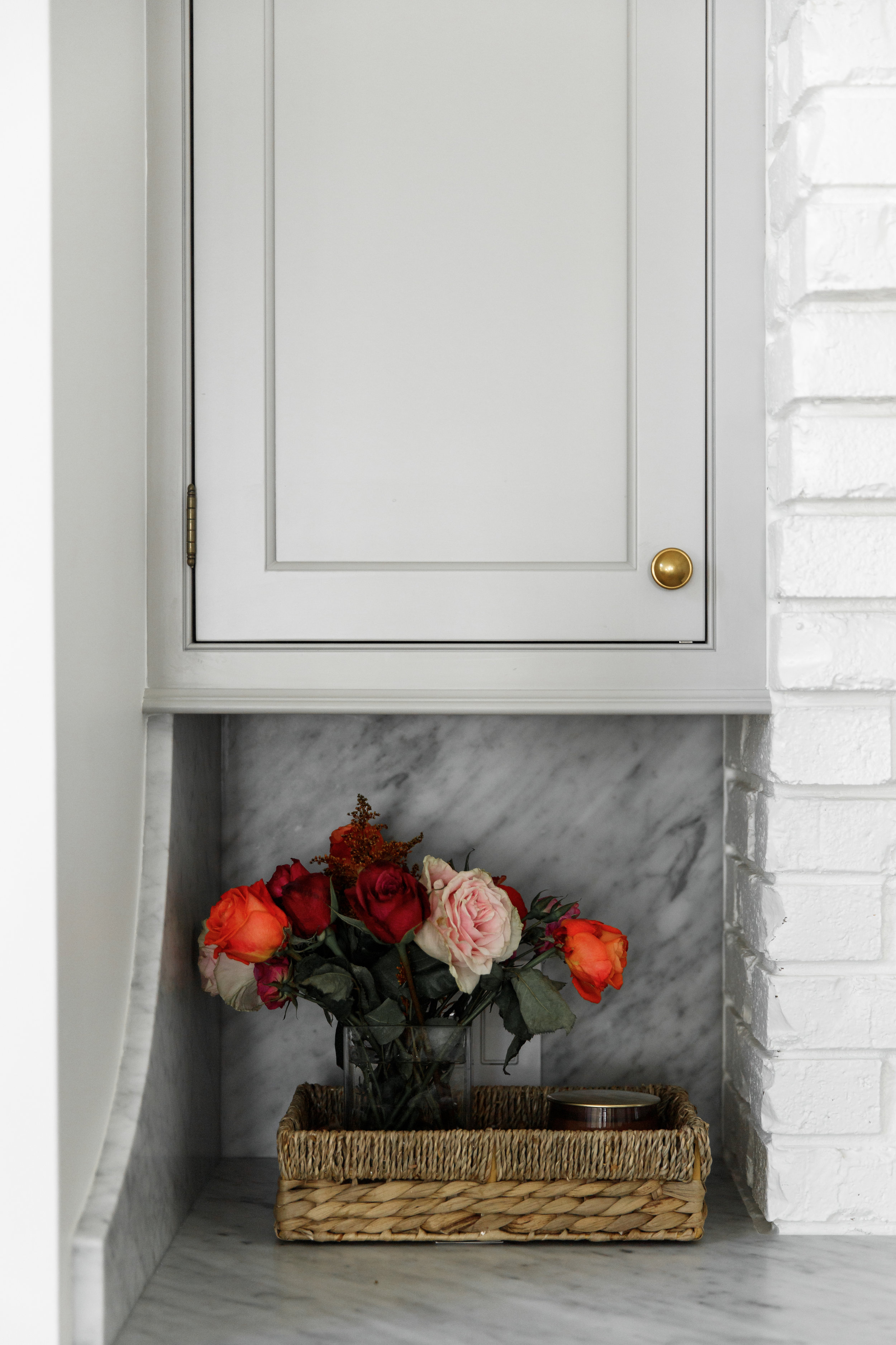 Light gray cabinets with gold hardware, flowers, rope basket and full height honed Carrara Marble countertops with backsplash.