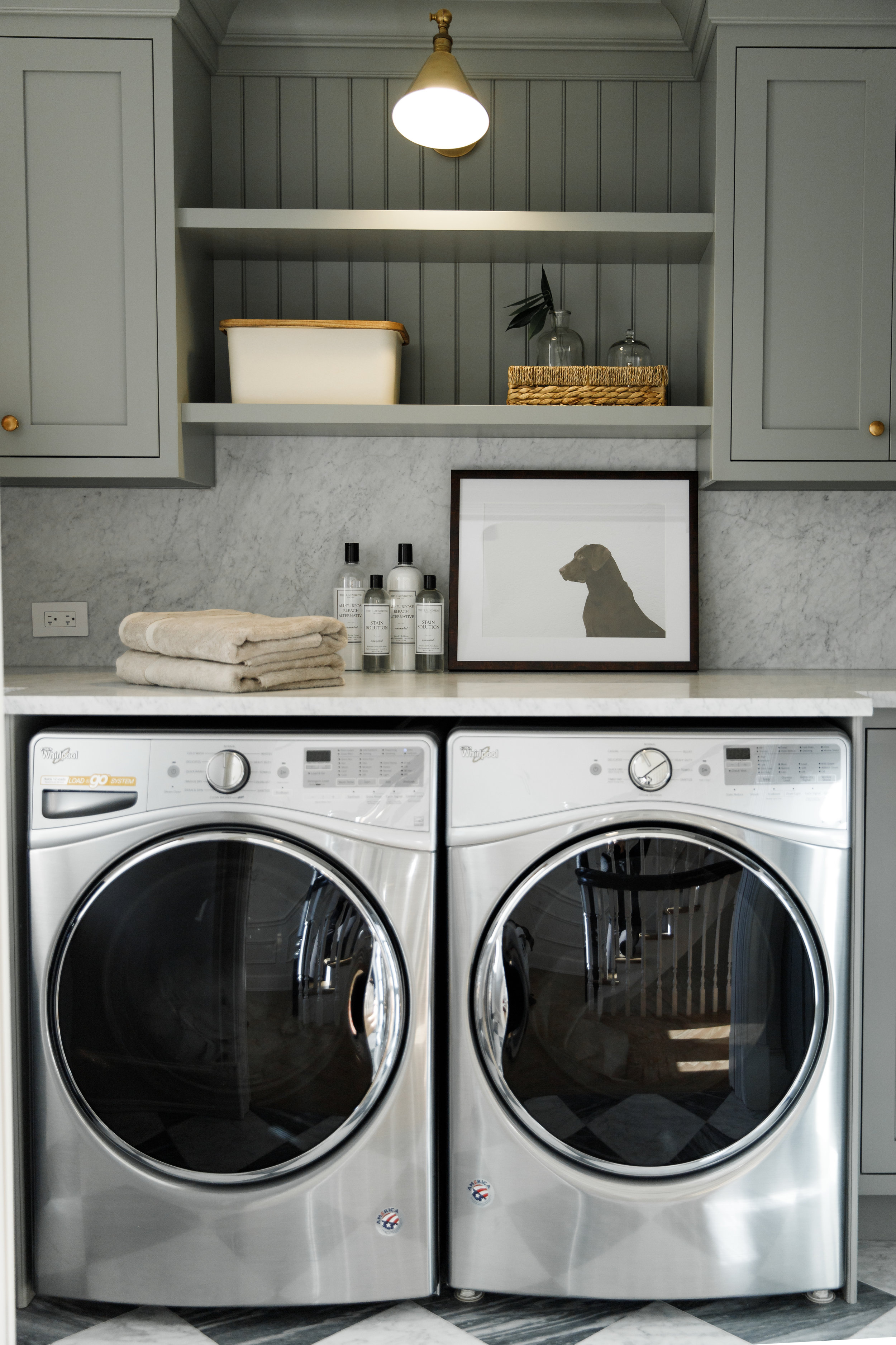 Laundry Room with custom cabinets, gold hardware and full height marble backsplash