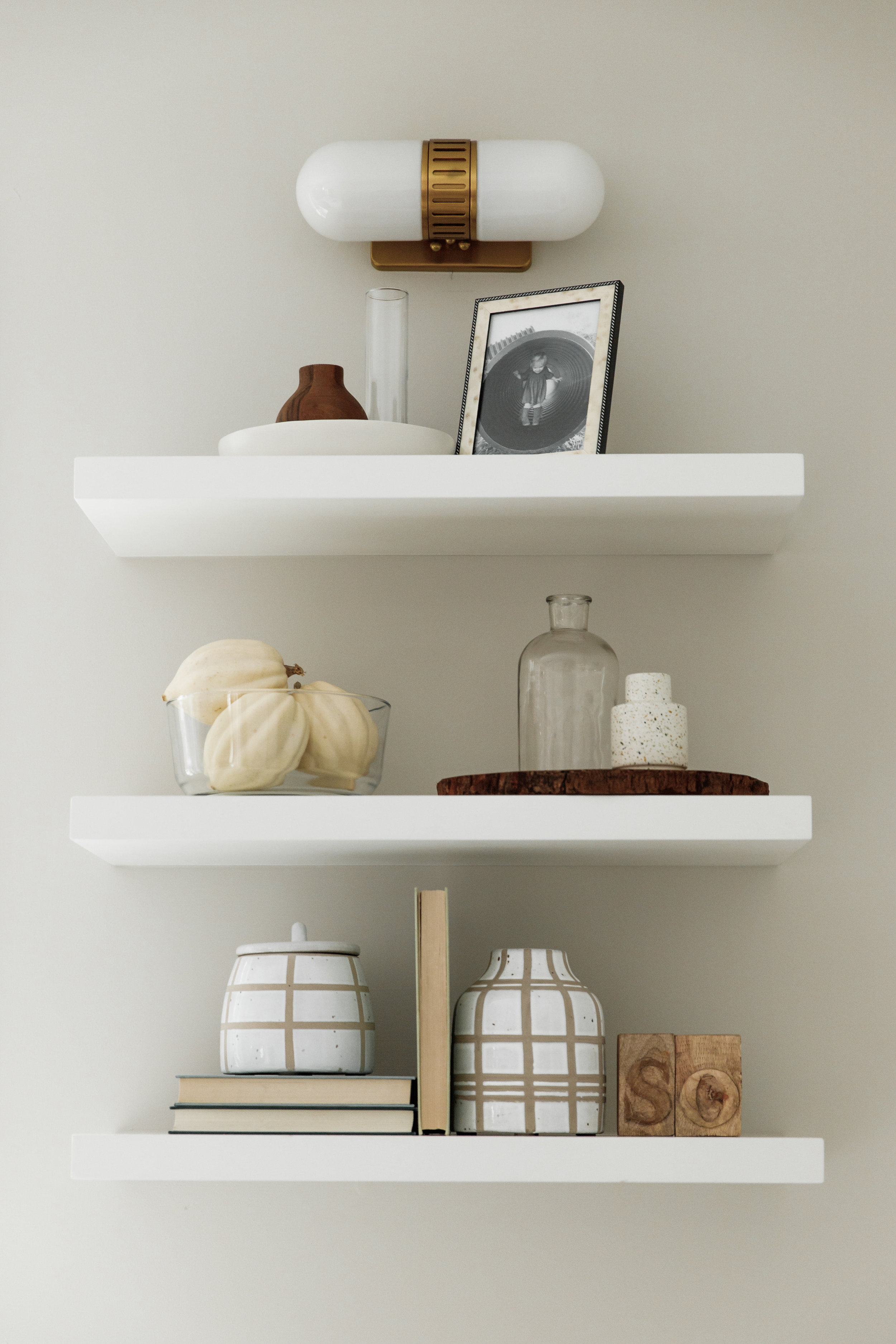 White kitchen with brass hardware and oak floors | shelf styling