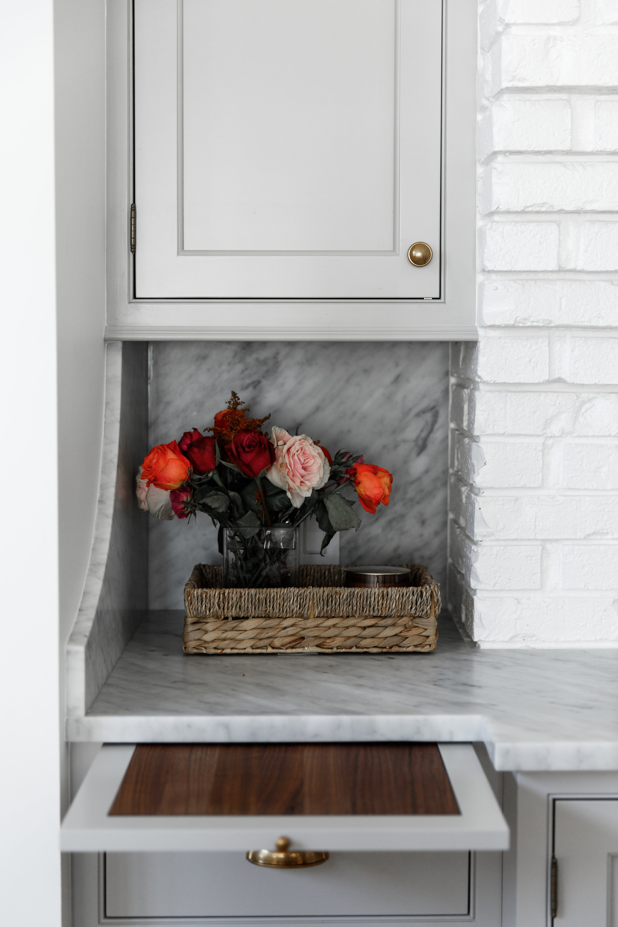 Kitchen cabinets with cutting board and marble backsplash