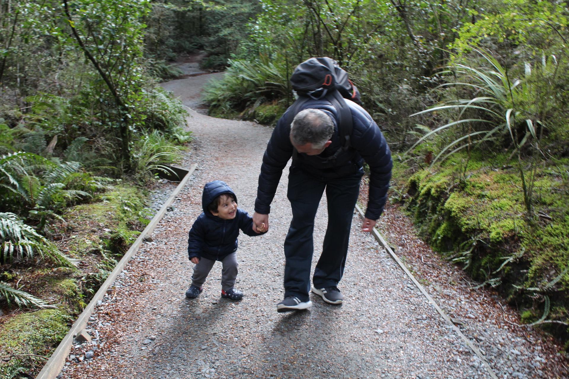 """Antonio brincando de andar """"que isso"""", com o papai, na trilha."""