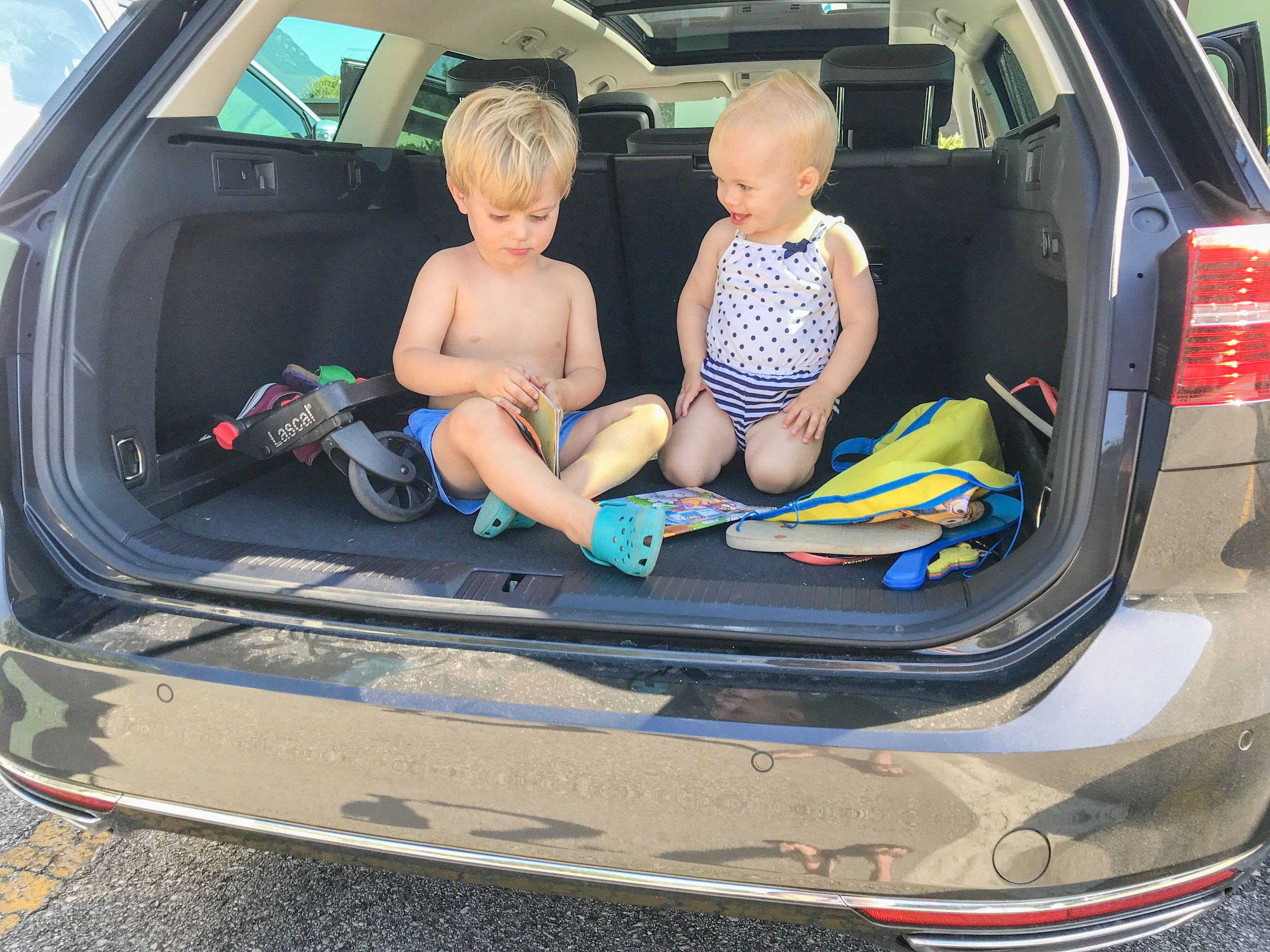 Elliot (almost 3) and amelia (17m) in the trunk after unloading the car in italy.