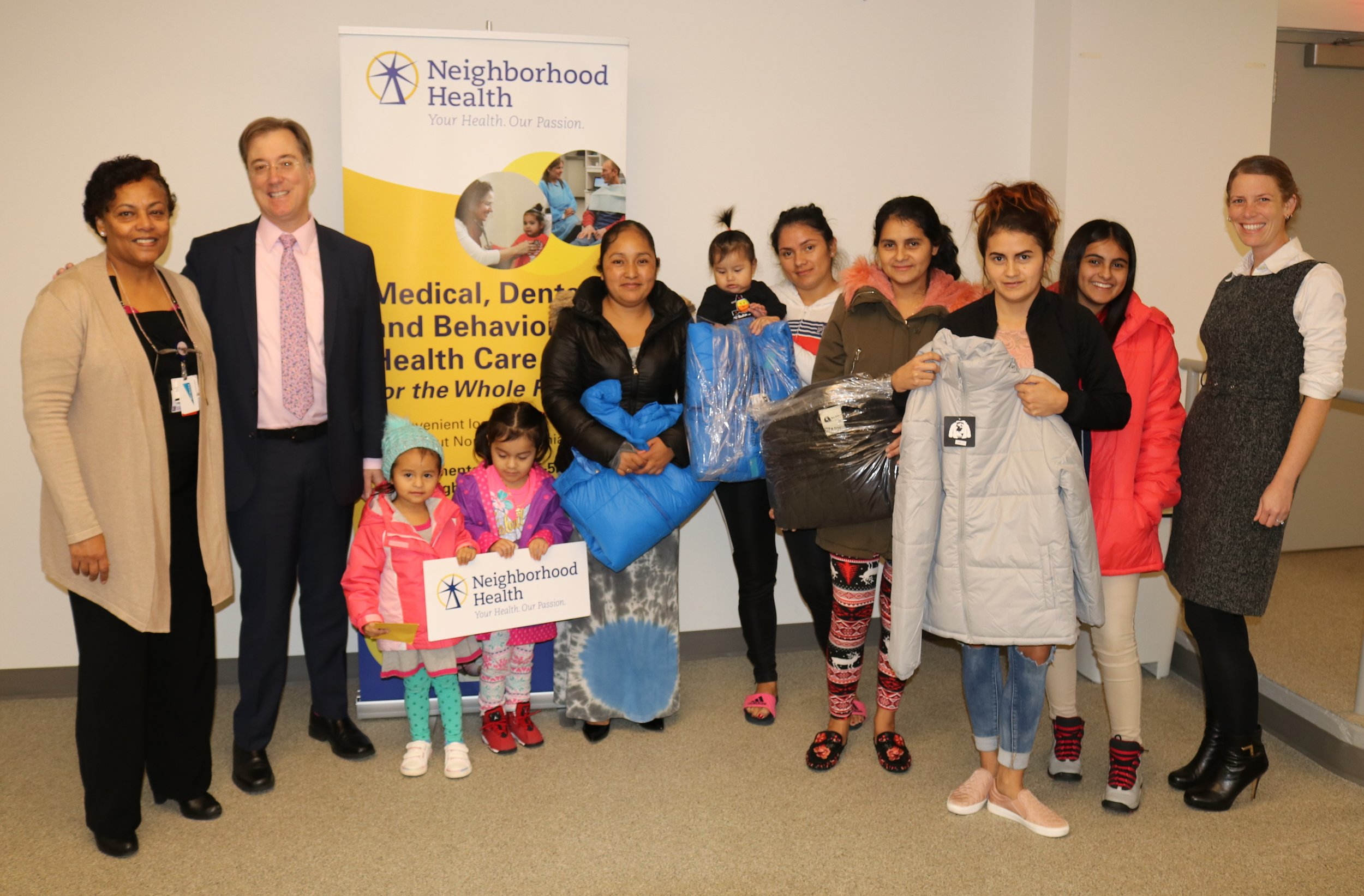 Christian Relief Services Executive Director Paul Krizek with Neighborhood Health Director of Behavioral Health Courtney Riggle-van Schagen, LCSW, right, and Family Support Supervisor Hirut Belete, left, with moms and children grateful to receive a new winter coat.