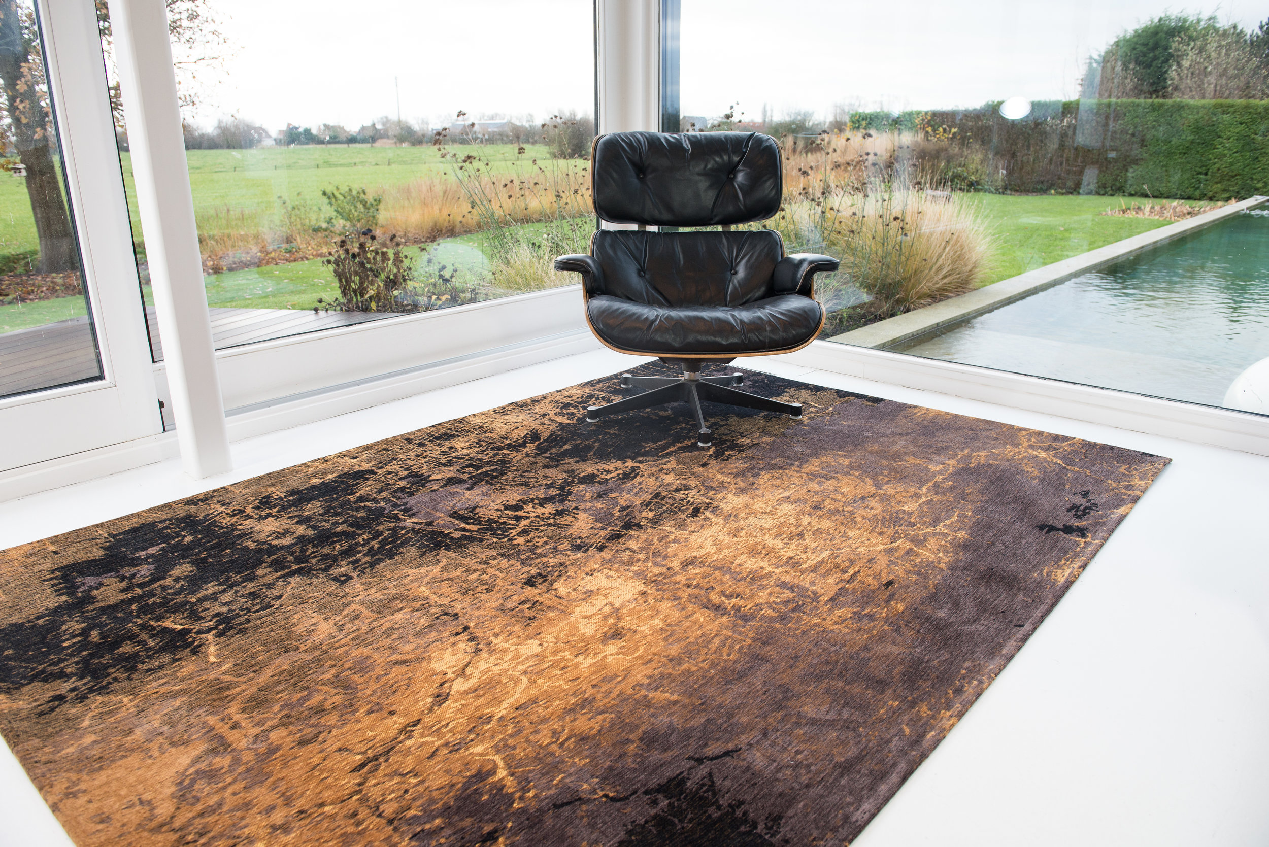 Modern, contemporary home with Louis de Poortere rug entitled Cracks in Deepmine in gold and black.