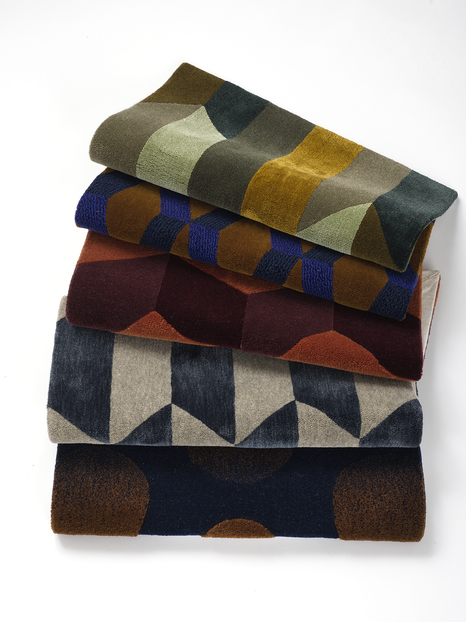 A stack of hand-tufted, silk wool rugs in jewel tones with different geometric patterns.