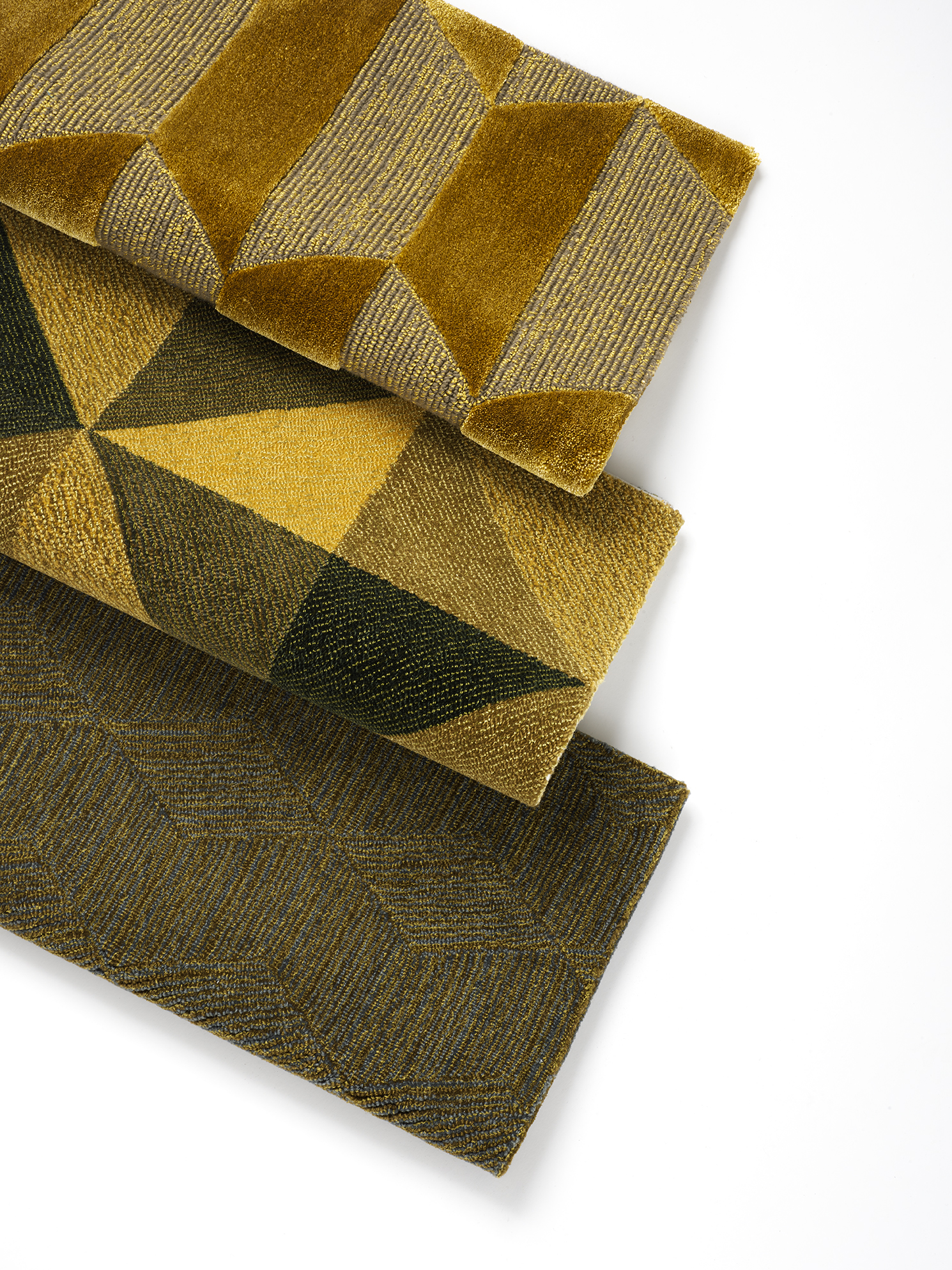 A stack of hand-tufted, silk wool rugs in natural tones with different geometric patterns.