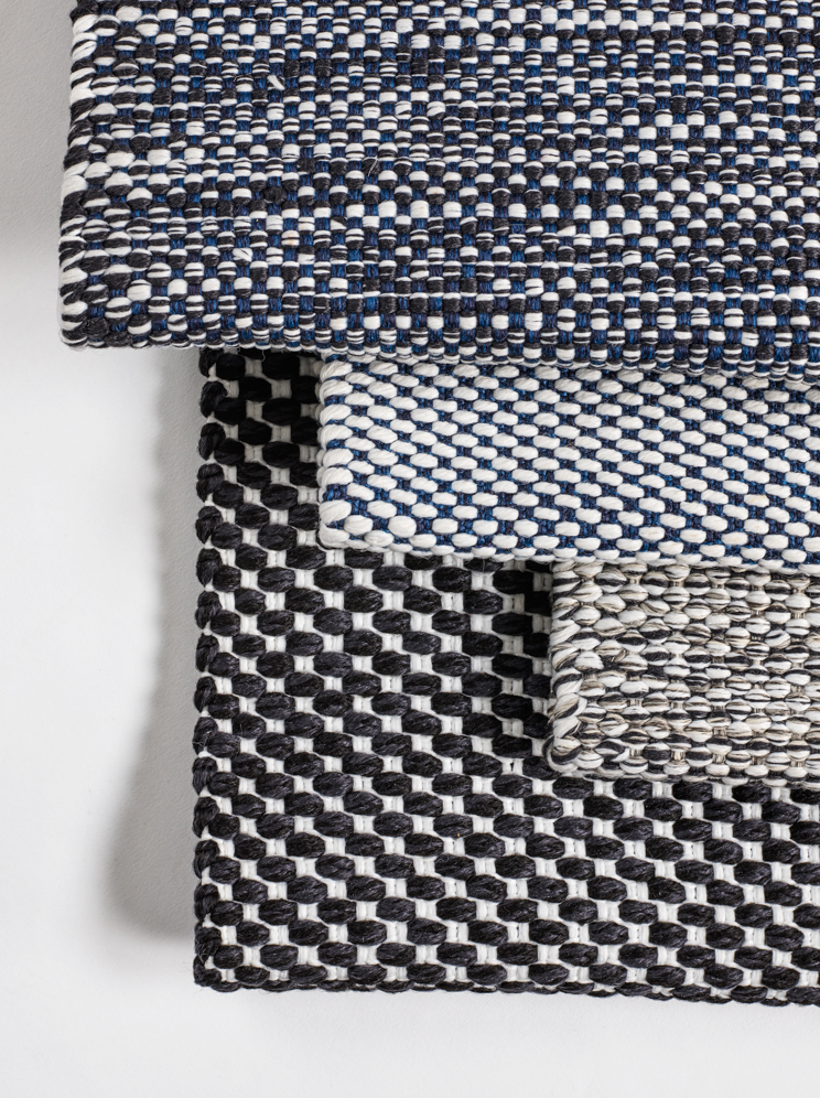 Stack of woven polypropylene outdoor rugs with geometric pattern in black and grey.
