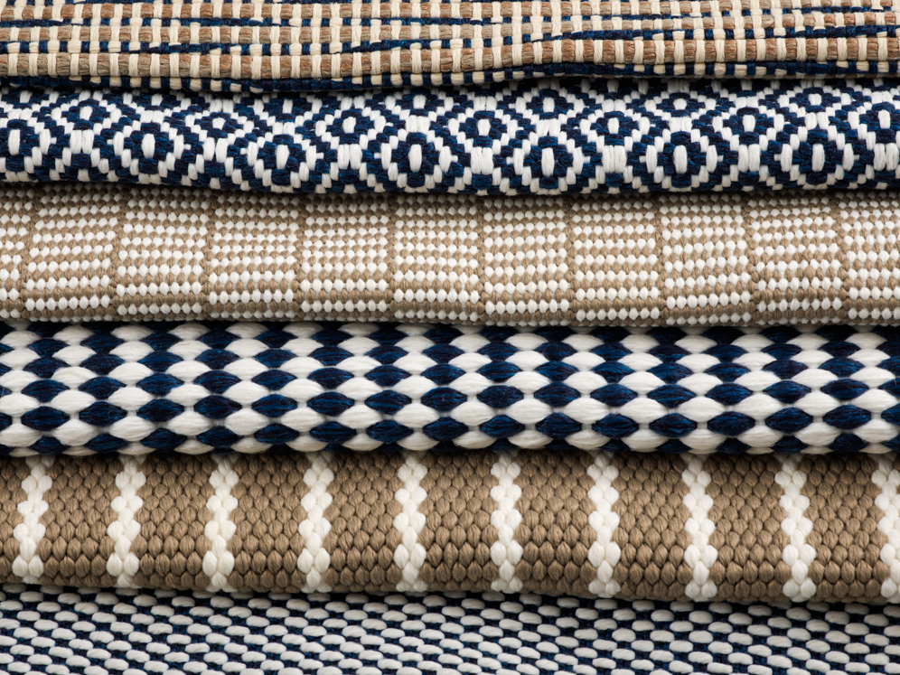 Stack of woven polypropylene outdoor rugs with geometric pattern in black and taupe.