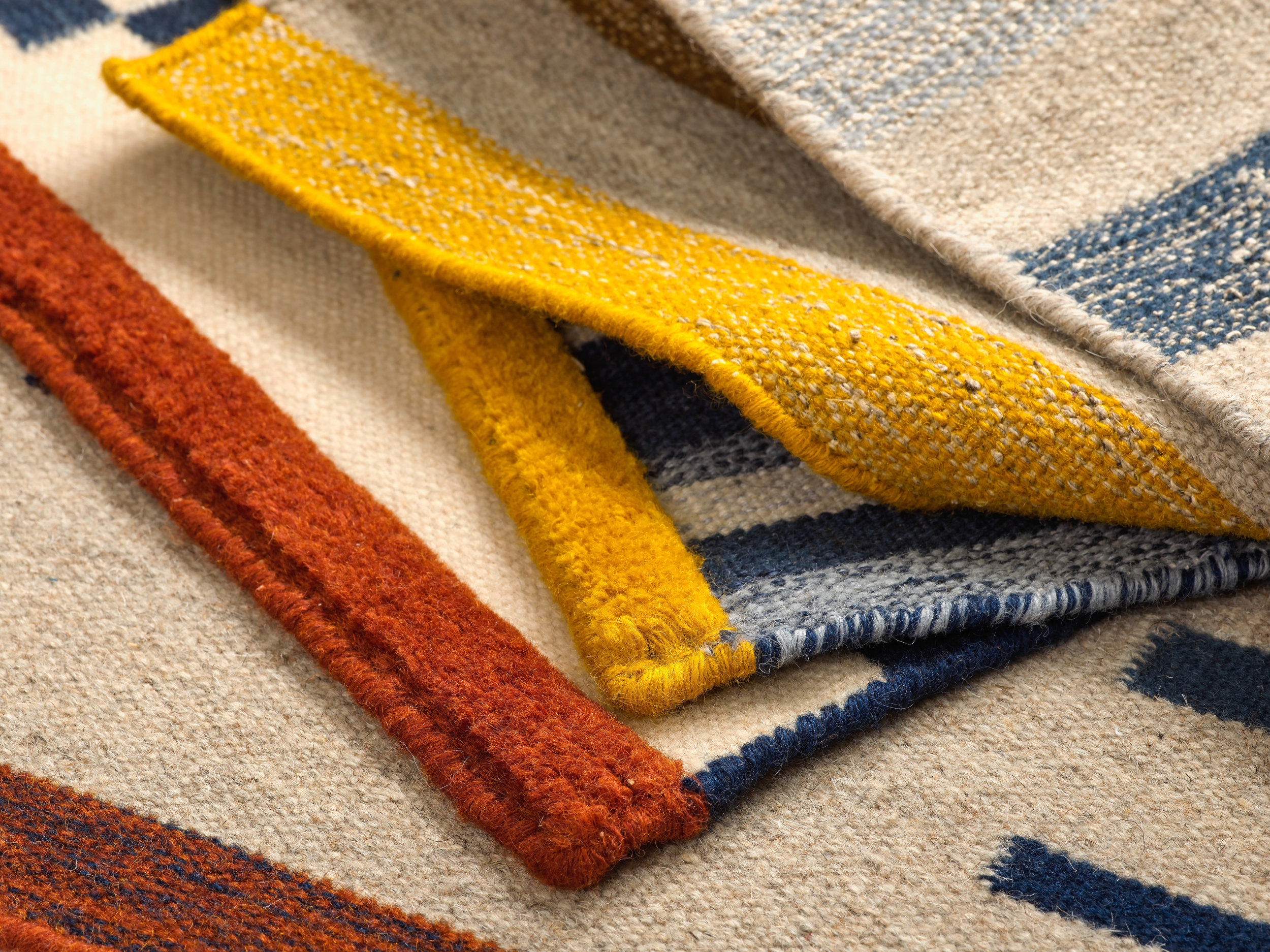 A stack of hand-knotted wool nettle rugs with abstract custom designs in red, blue, yellow and cream.