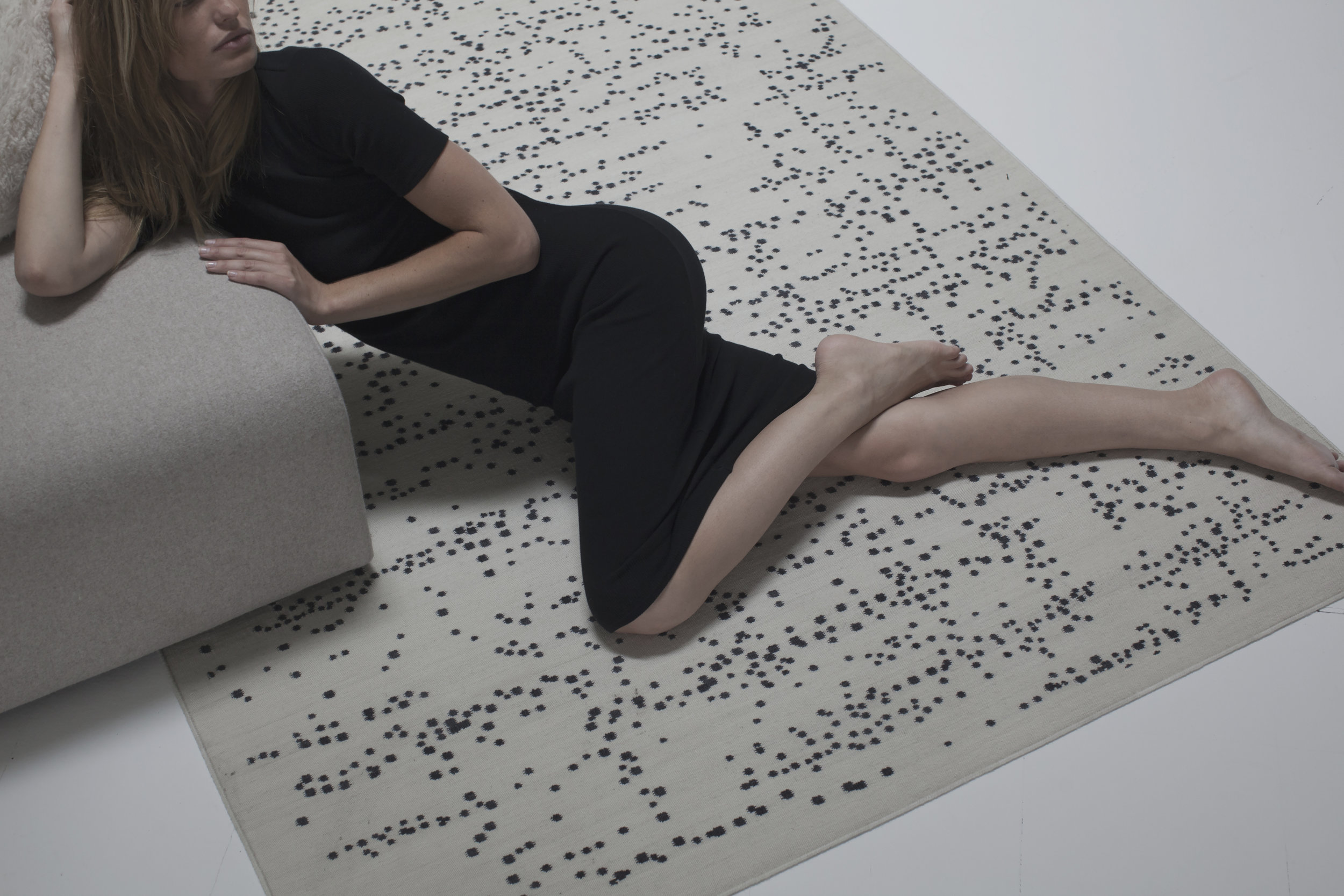 Woman laying on Dropp Area Rug.