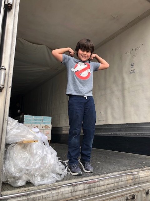 Grayson Moody, son of the Fruit Sale Chair, helping the Rowing Club unload the truck.