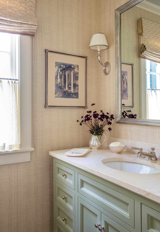 Silver framed mirror mounted on wall in bathroom