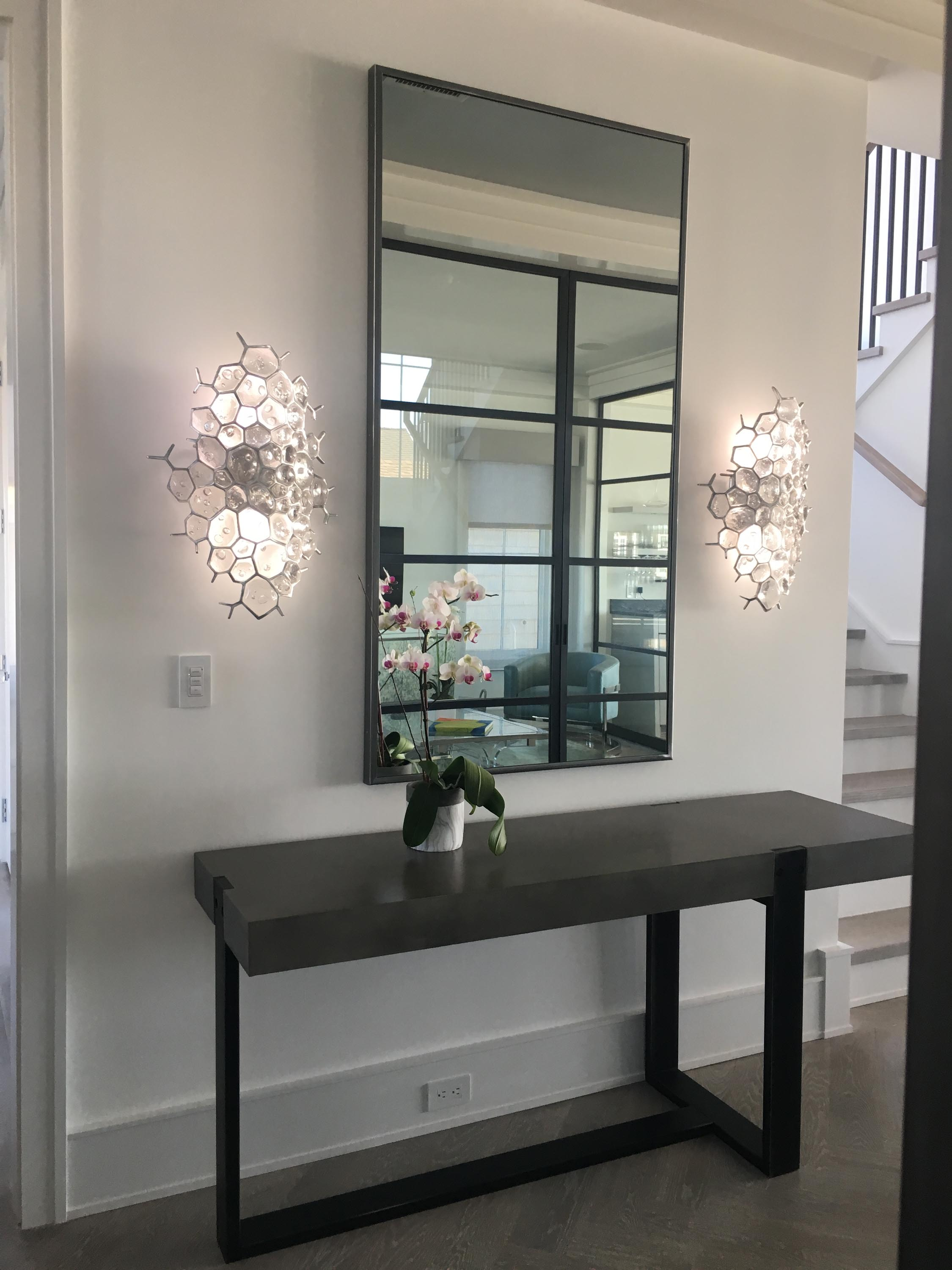 Slim framed mirror hanging over wooden console table