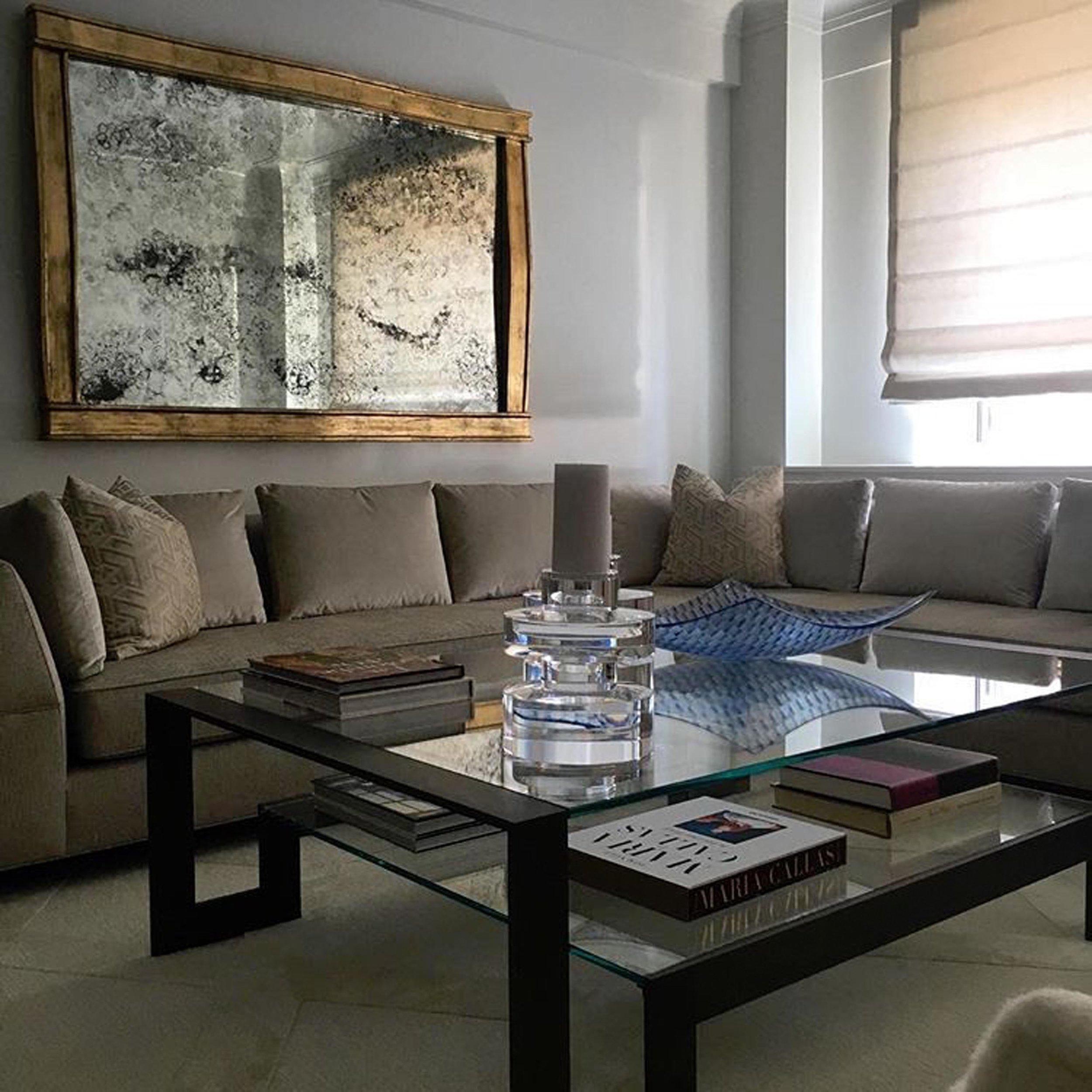 Textured brass rectangular framed mirror hanging over sectional sofa