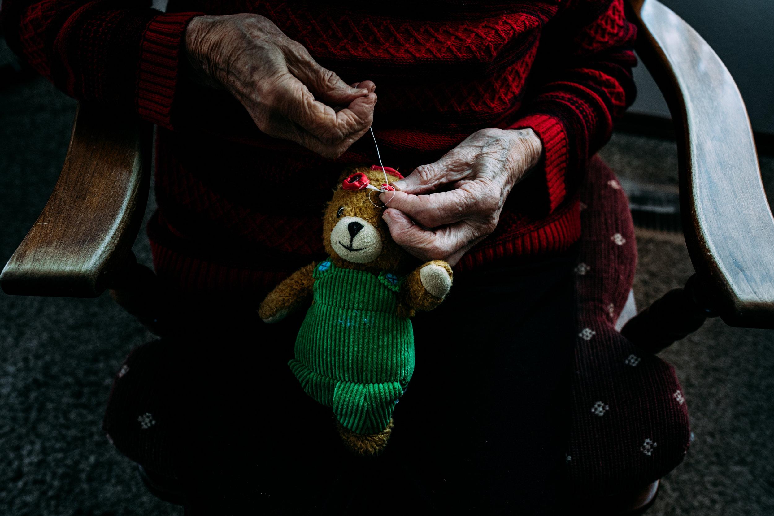 great grandma sews teddy bear for documentary family photography - anna nodolf