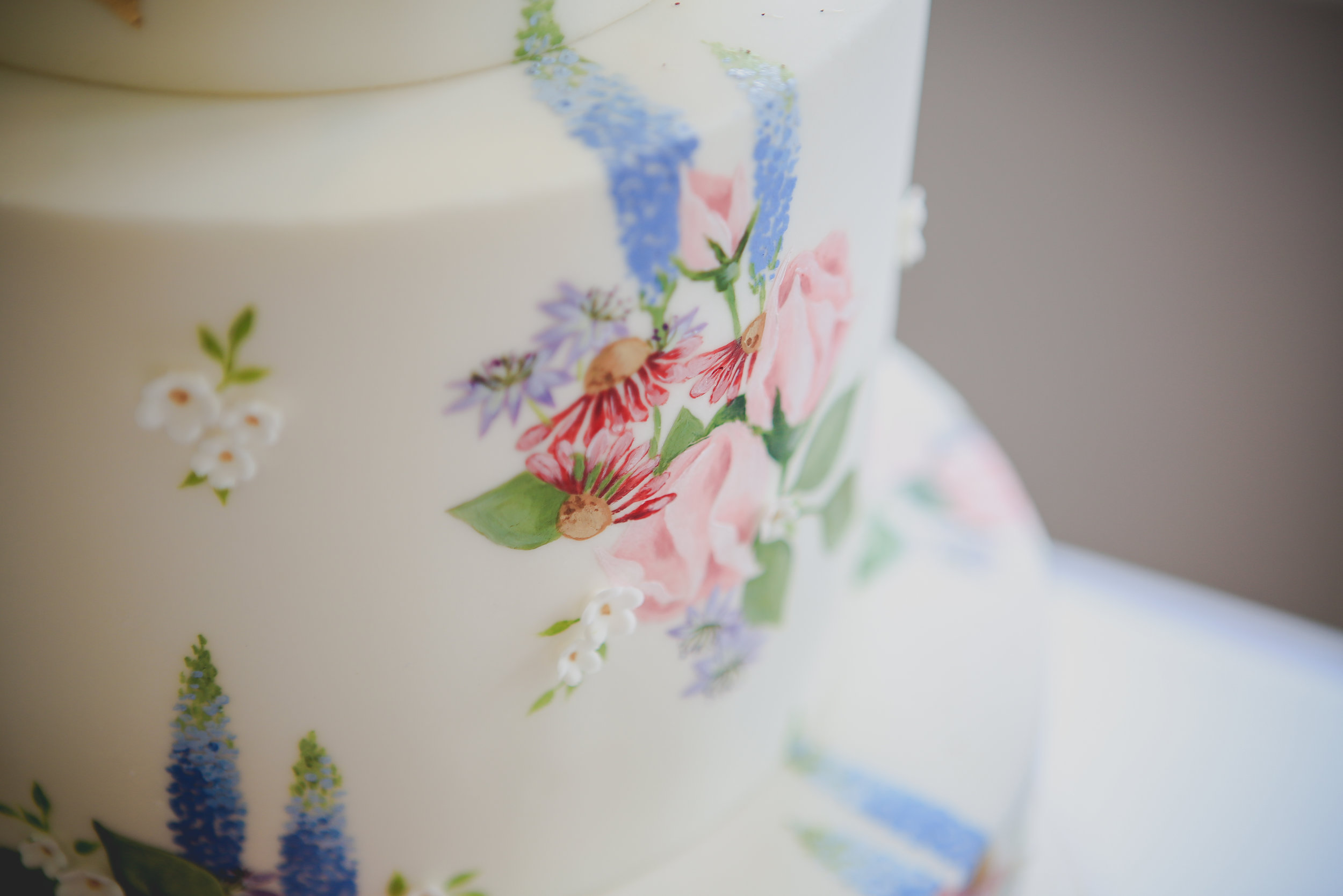 CORNISH WILDFLOWERS  This pretty 3 tier cake is hand painted with Cornish wildflowers and finished with decadent gold leaf and a pretty posy of fresh blooms... perfect for a country garden wedding.