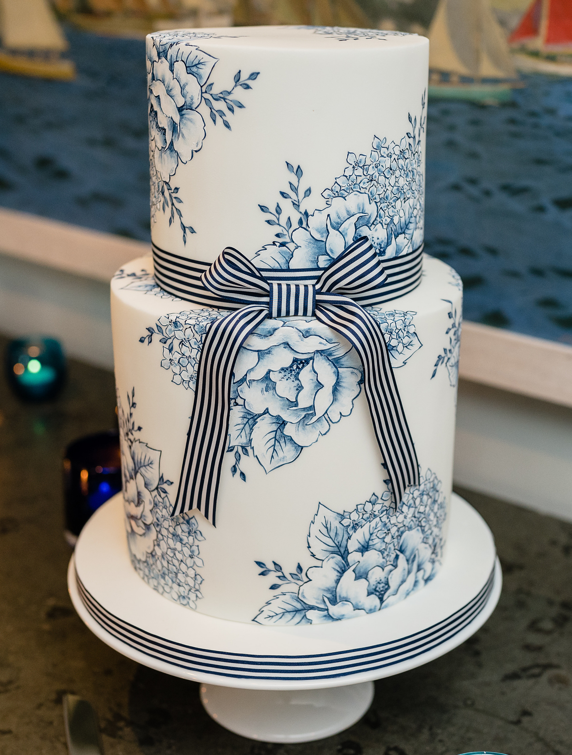 NAUTICAL STRIPES AND FLOWERS  A delicate hand painted design in blue and white enhanced by a bold striped ribbon. This design is a favorite for nautical themed weddings and can be recreated over any number of tiers.