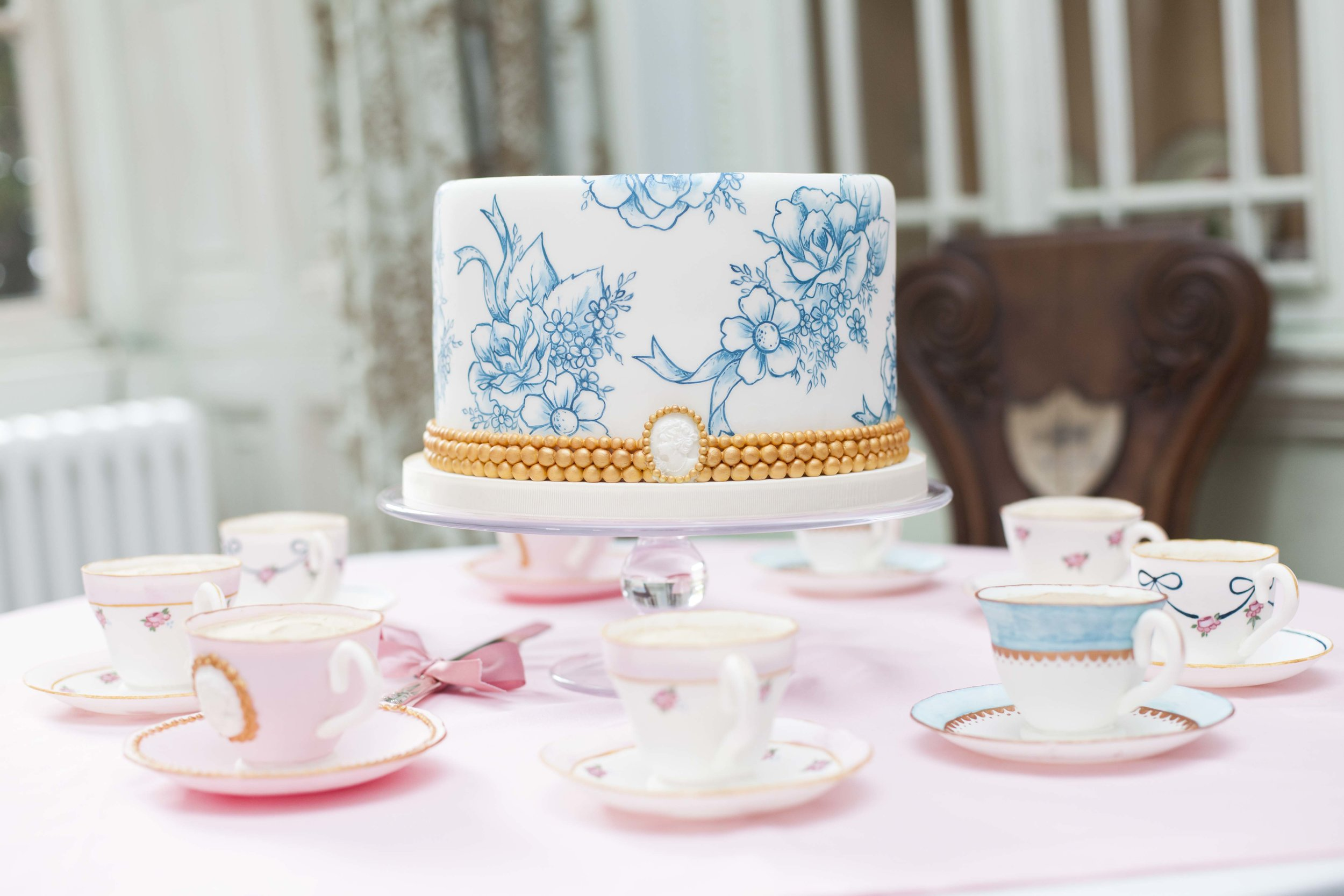 TOILE DU JOUY  A hand painted single tier cake for an intimate celebration decorated with a Toile Du Jouy pattern in blue and white. The cake is surrounded by edible teacups and saucers hand painted to complement the cake - these were given as special gifts to members of the bridal party.