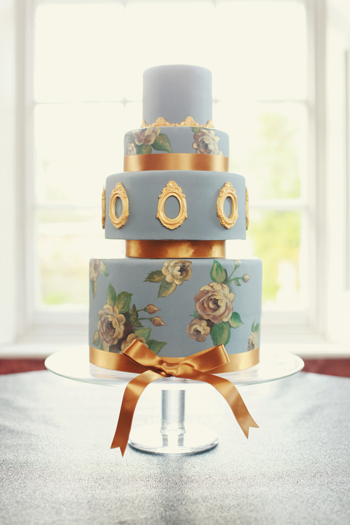 PEWTER AND GOLD  A pewter and gold wedding cake with hand painted roses and moulded gold frames. I love a statement cake with a dramatic coloured background!