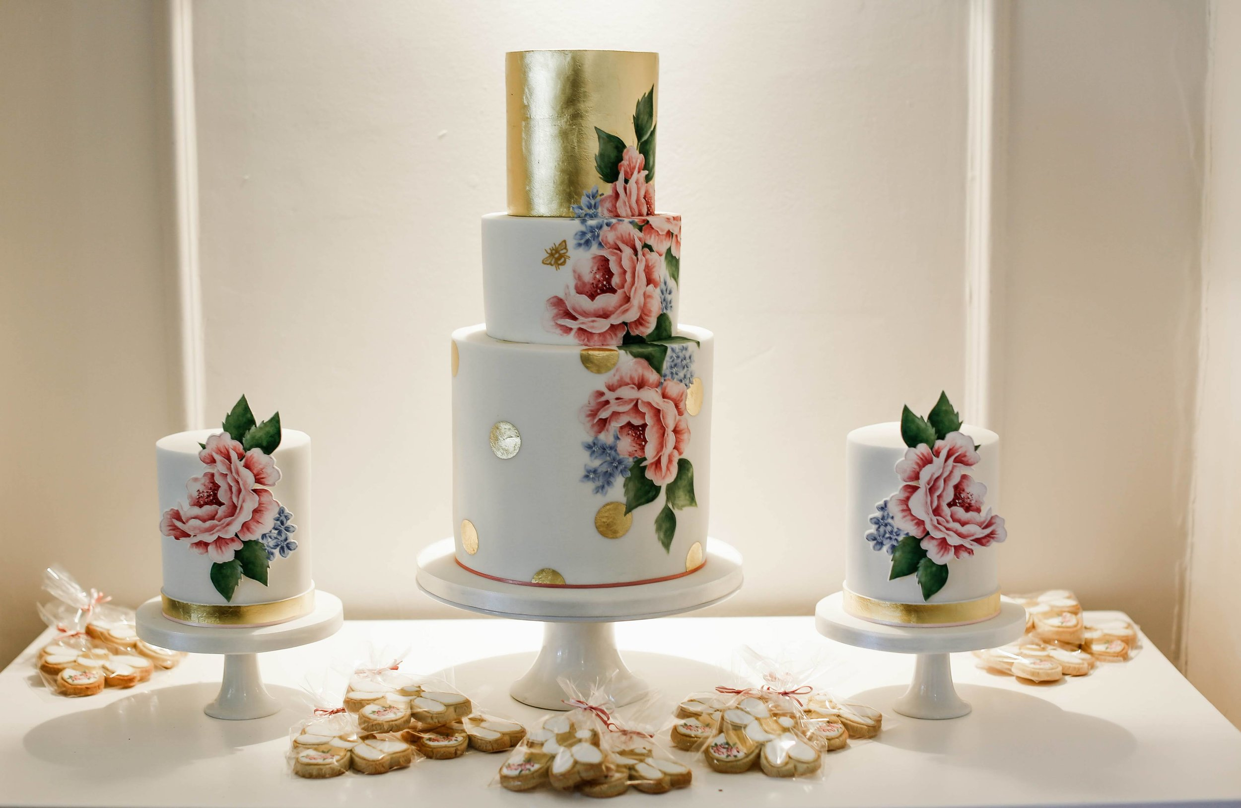 ROSES AND GOLD POLKA DOTTY  This trio of cakes is a real showstopper! A focal 3 tier cake with a 24ct edible gold leaf top tier and hand painted floral design flanked by 2 single tier cakes finished with gold leaf bands and hand painted pastillage panels. The cake was artfully displayed on a vintage dressing table to give it real wow factor!