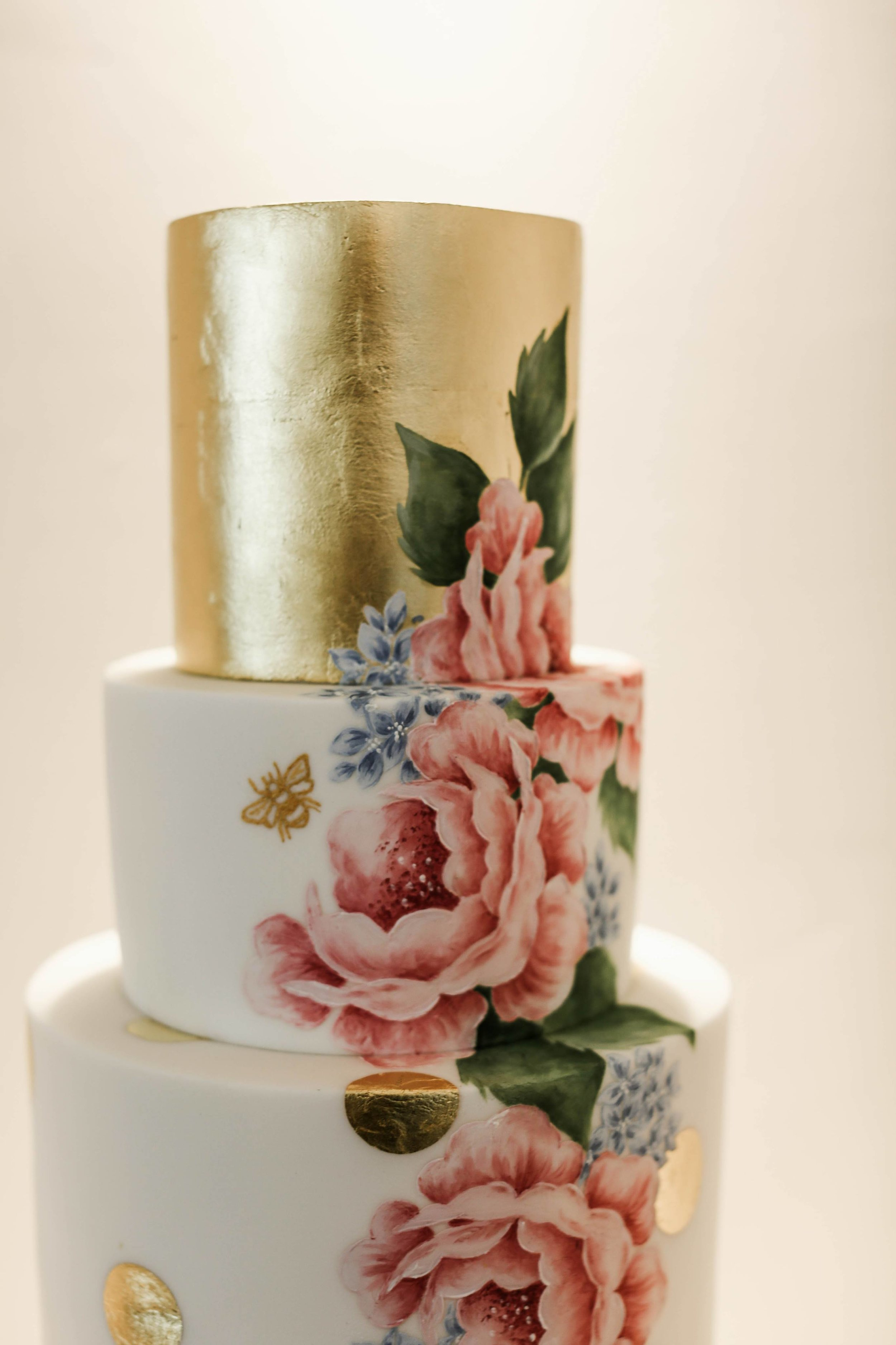 ROSES AND GOLD POLKA DOTTY  A 3 tier cake with gold leaf covered top tier and gold polka dots with a hand painted floral design