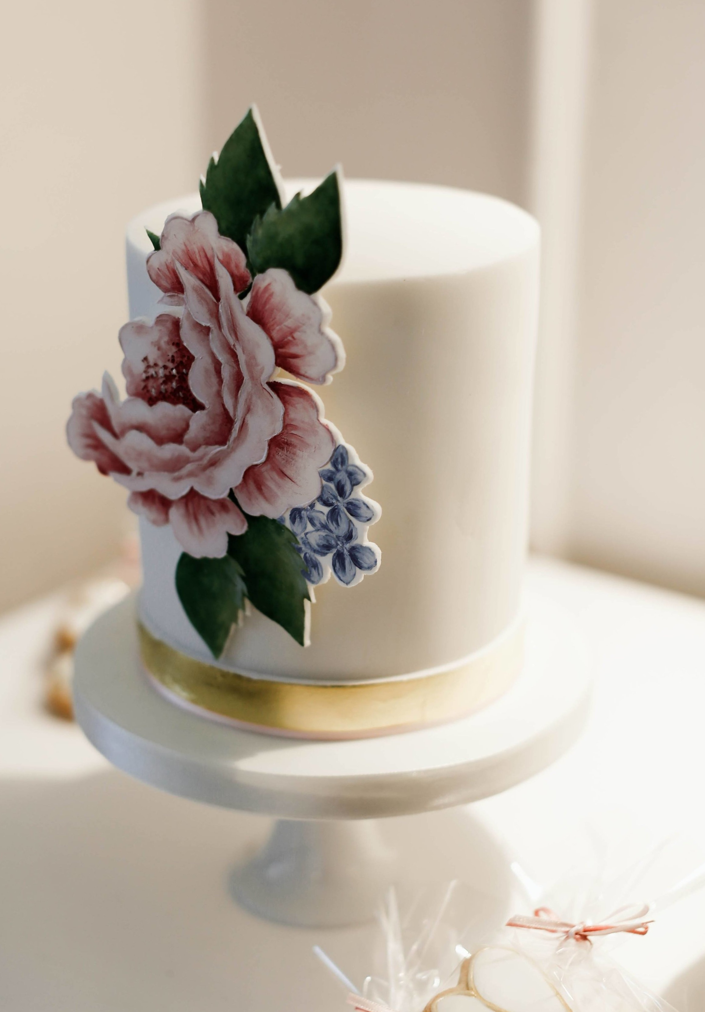 MINI ROSE CAKE  A mini cake with an edible gold leaf band around the base finished with a hand painted rose flat sugar panel.